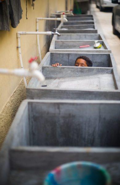 """""""Alejandro"""", hijo de Marcos, juega en el área de lavado de una cuartería"""