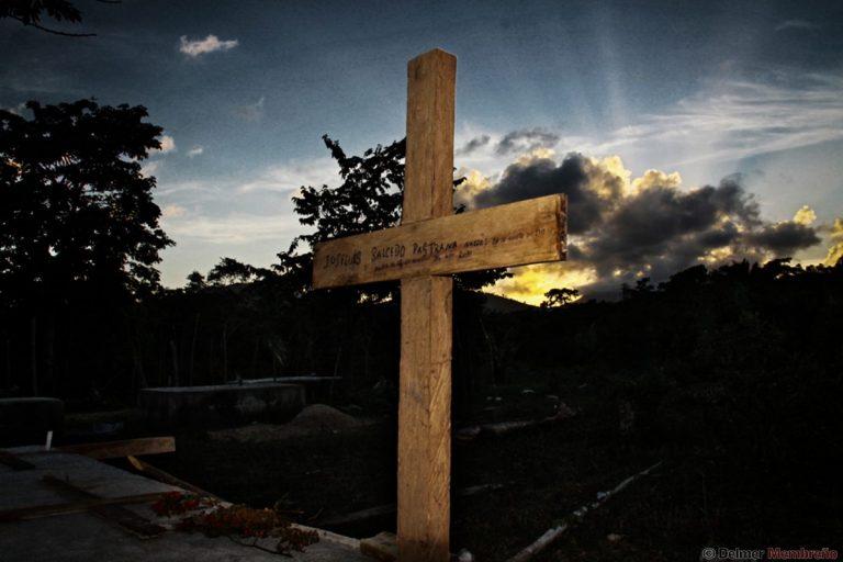 """La cruz de la imagen señala el lugar donde se encuentra sepultado el campesino José Luis Salcedo Pastrana, quien, en la mañana del 15 de noviembre de 2010, junto a 160 campesinos del Movimiento Campesino del Aguán (MCA), se dirigió a la plantación Tumbador con el propósito de recuperar las tierras que por derecho propio les pertenecen, terminando, según un informe preliminar policial, en un """"enfrentamiento"""", que cobró la vida de Salcedo Pastrana y cuatro campesinos más."""