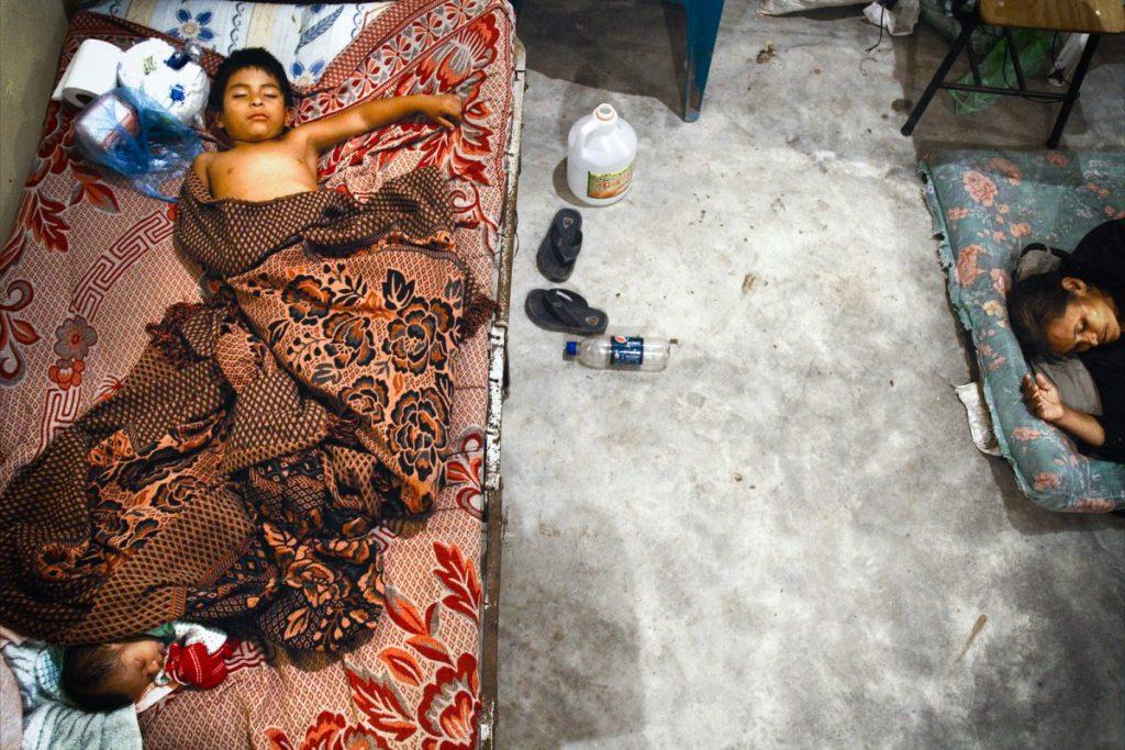 Una madre y sus hijos descansan en un improvisado albergueUna madre y sus hijos descansan en un improvisado albergue