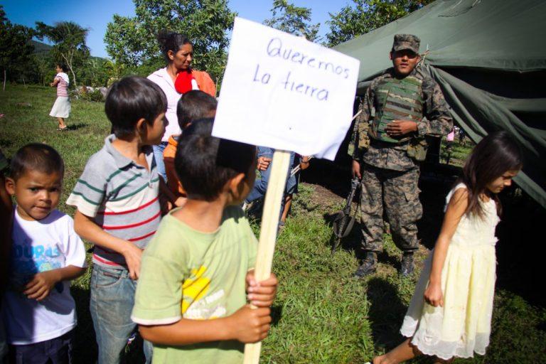 Varios niños protestan frente a una carpa militar instalada en la aldea Guadalupe Carney en Trujillo, Colón, Honduras.