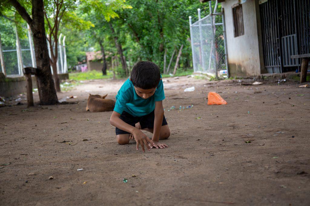 Un niño juega con sus mables en una calle frente a su casa en la comunidad de Namasigüe, 30 de mayo de 2019. Foto: Martín Cálix.