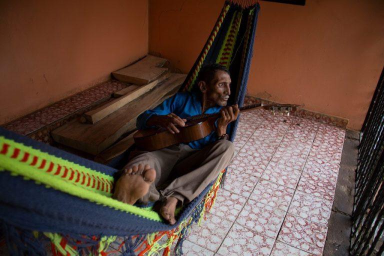 El padre de Elva toca la guitarra mientras descansa en su hamaca, Namasigüe 30 de mayo de 2019. Foto: Martín Cálix.