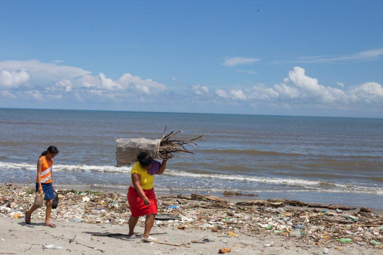 Lesly y su hija Emily —la mayor de sus 3 hijas— vuelven a su casa luego de recoger trozos de madera y plásticos para poder cocinar sus alimentos. Esta madre soltera y sus hijas se mudaron a la comunidad de la Barra del Río Motagua en 2017, cuando el padre de sus hijas las abandonó, aquí encontraron un hogar en una comunidad amenazada por la erosión costera y la contaminación debido a la basura que invade todo el año las playas de su comunidad. Omoa, Cortés, 29 de septiembre de 2020. Foto: Martín Cálix