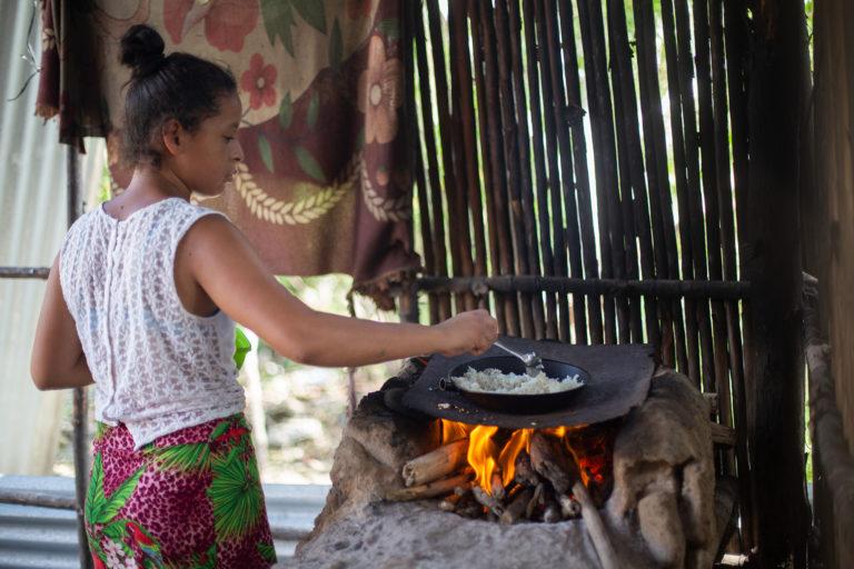 Leticia, la segunda hija de Lesly, cocina arroz para el almuerzo en una hornilla de barro que suelen encender con plásticos y trozos de madera que recogen de la playa. Omoa, Cortés, 29 de septiembre de 2020. Foto: Martín Cálix
