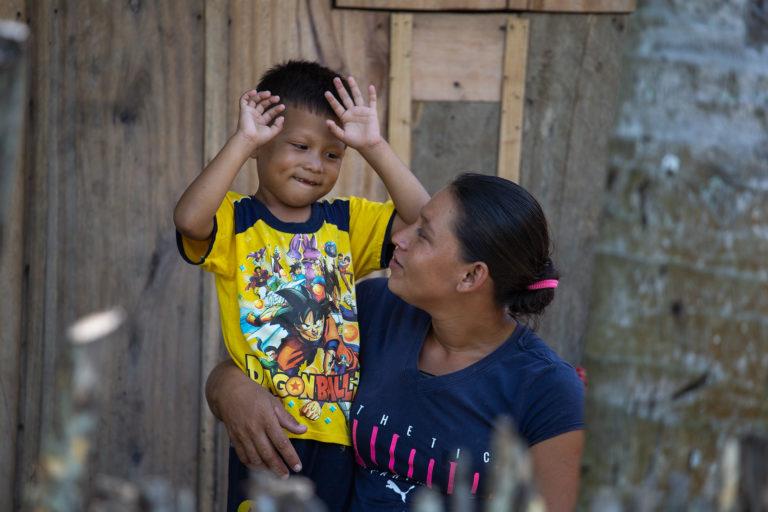 Aldair juega en brazos de su madre Dania en la entrada de su casa hecha de madera y levantada en pilones de concreto por las constantes inundaciones en la comunidad de la Barra del Río Motagua. Omoa, Cortés, 28 de septiembre de 2020. Foto: Martín Cálix