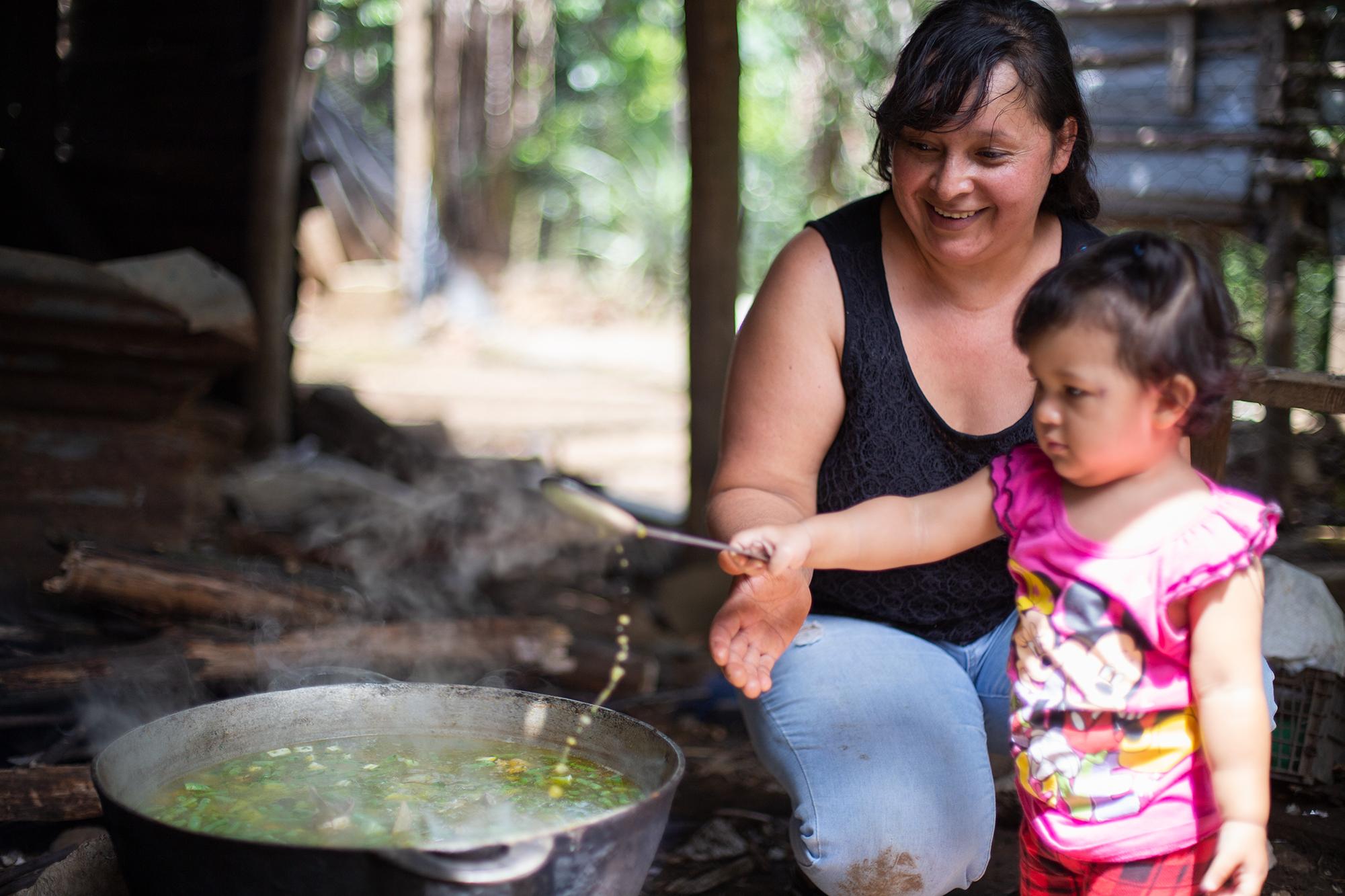 Dina junto a su nieta de dos años mientras cocina una sopa de gallina para el almuerzo que ha encargado la CNTC, quien suele contratarla para cocinar cuando la organización realiza talleres o jornadas con mucha gente. Chinacla, La Paz, 20 de octubre de 2020. Foto: Martín Cálix.