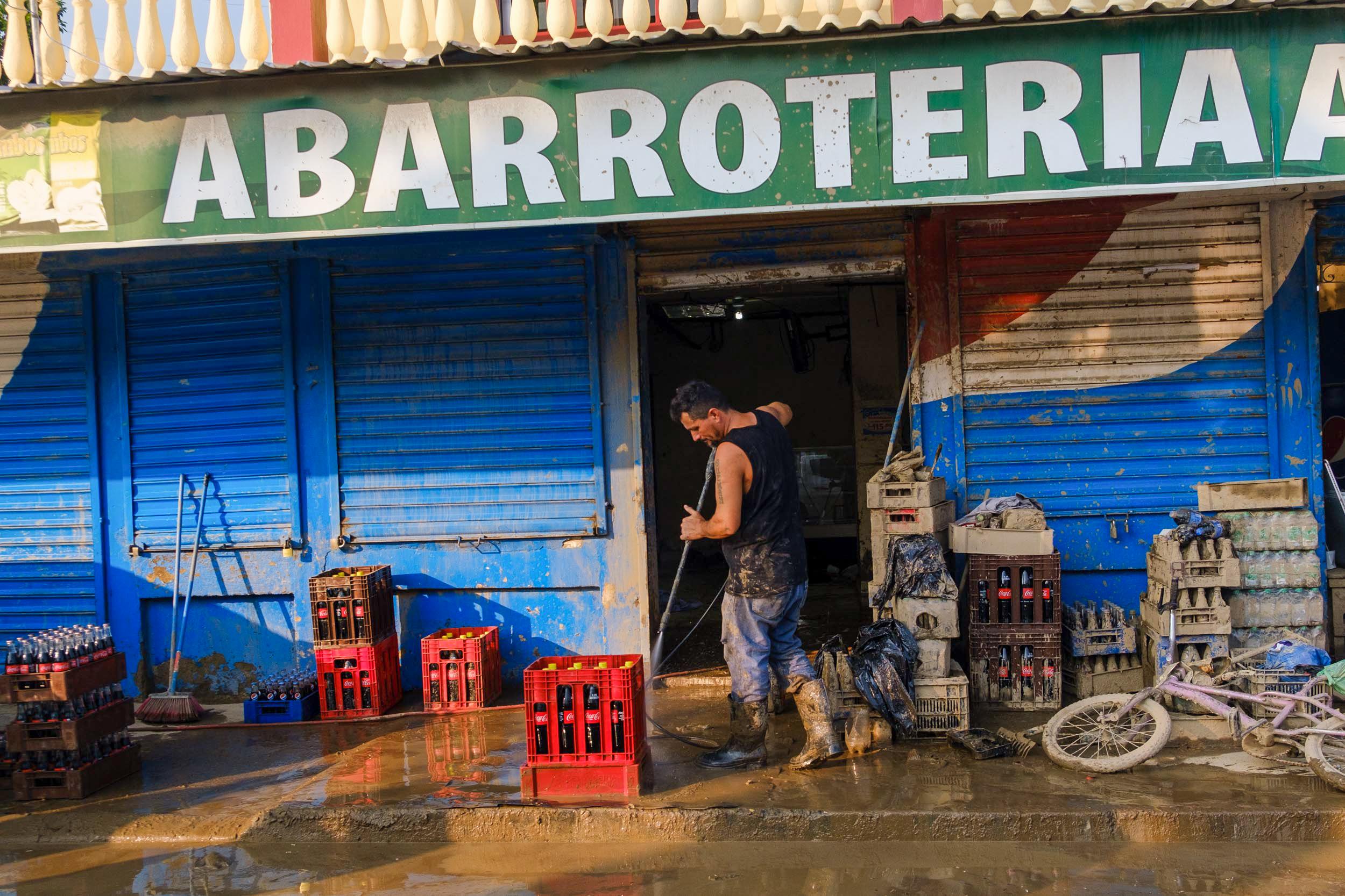 Este comerciante limpia su negocio y trata de recuperar algo de su producto, en la calle principal del sector Chamelecón. San Pedro Sula, 10 de noviembre de 2020. Foto: Deiby Yanes.