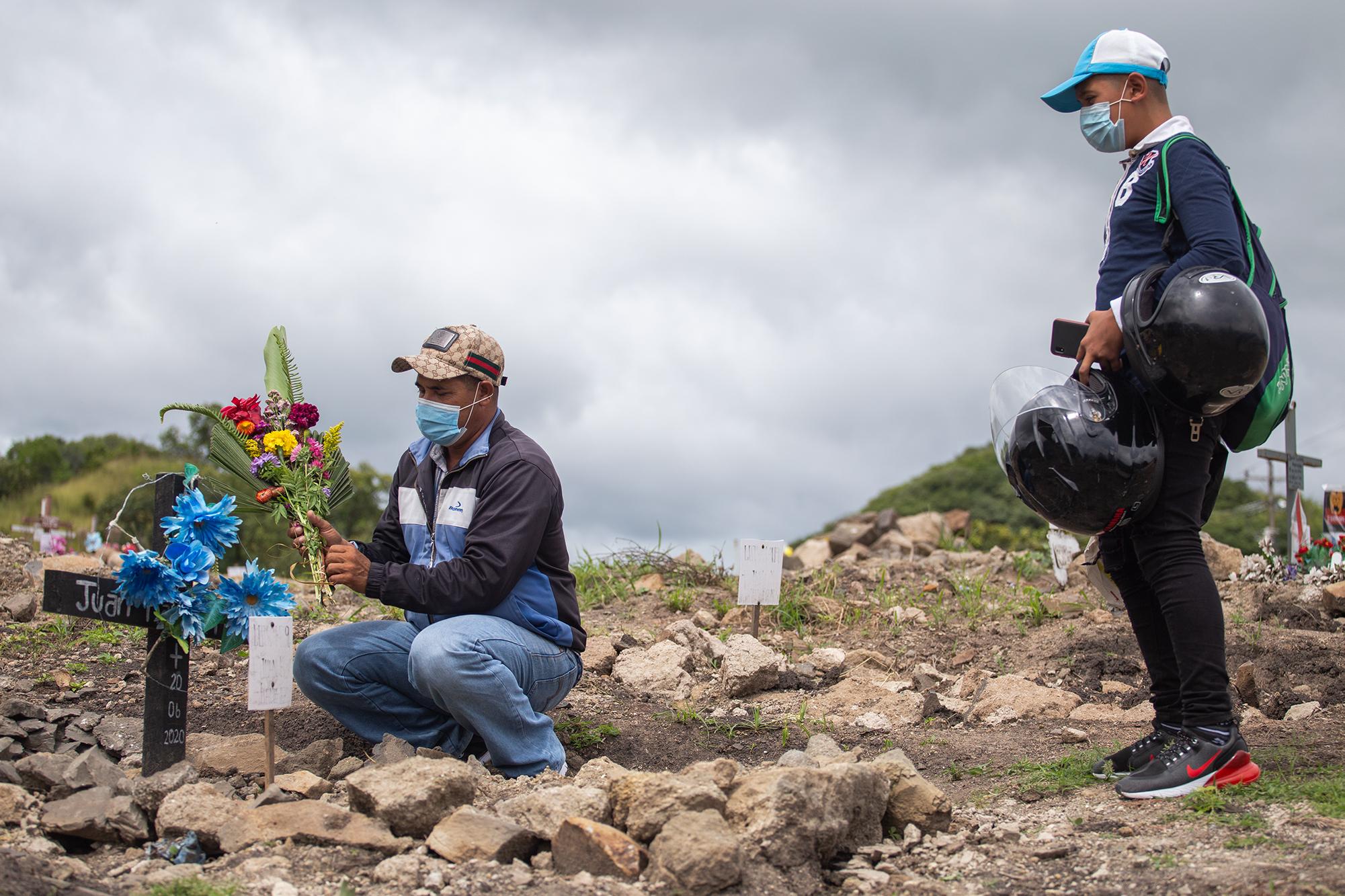 La tumba de Juan Ramón Ramírez, fallecido el 20 de junio, es limpiada y adornada con flores por su  hijo Jaime y su nieto. Comayagüela, 2 de noviembre de 2020. Foto: Martín Cálix.