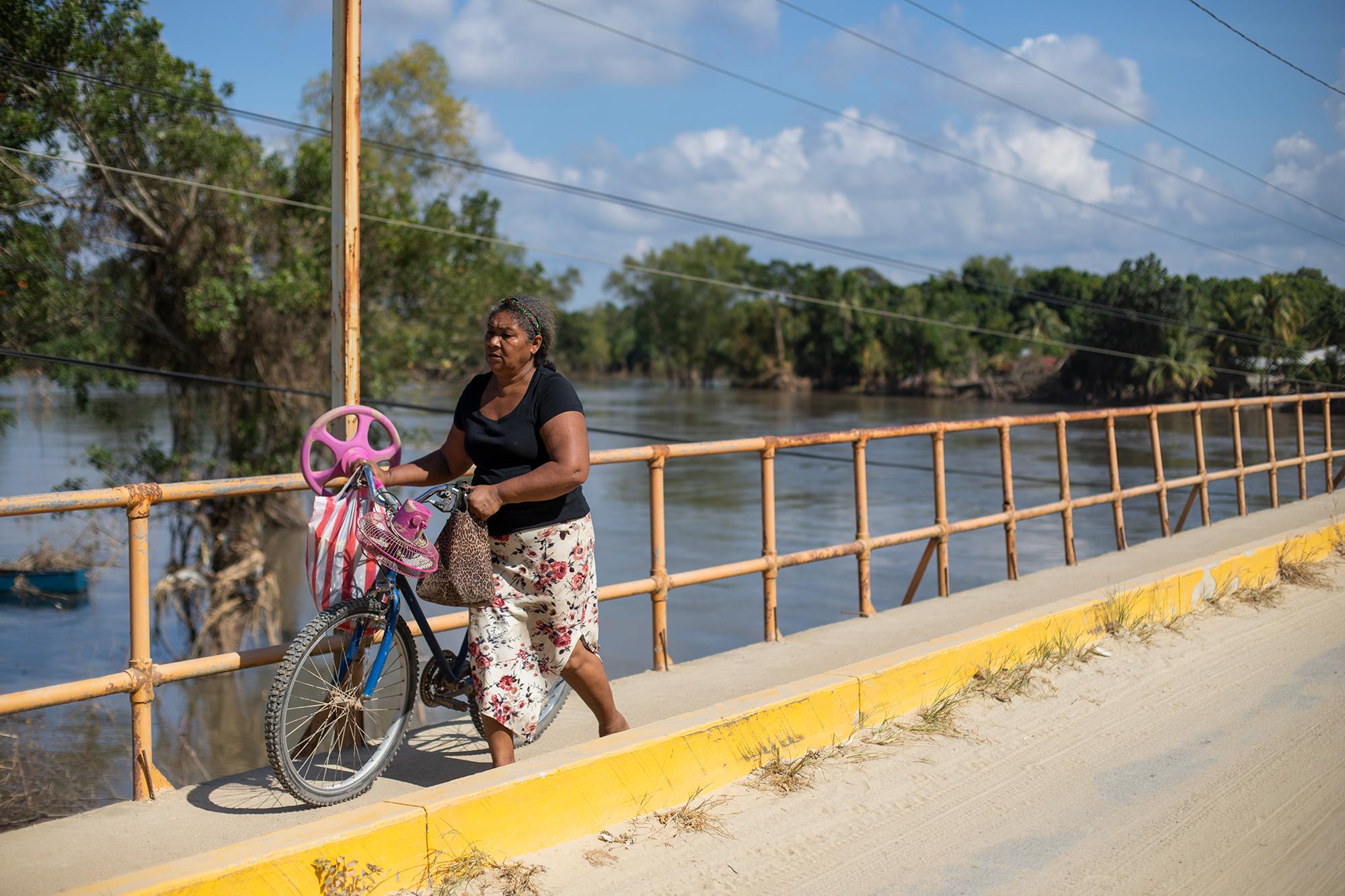 Una mujer atraviesa el puente bailey de la comunidad de Baracoa, un puente que según los pobladores podría venirse abajo y dejar incomunicadas la comunidades hacia adentro por el debilitamiento de la tierra que está cediendo ante la crecida del río Chamelecón. Baracoa, Cortés, 15 de noviembre de 2020. Foto: Martín Cálix.