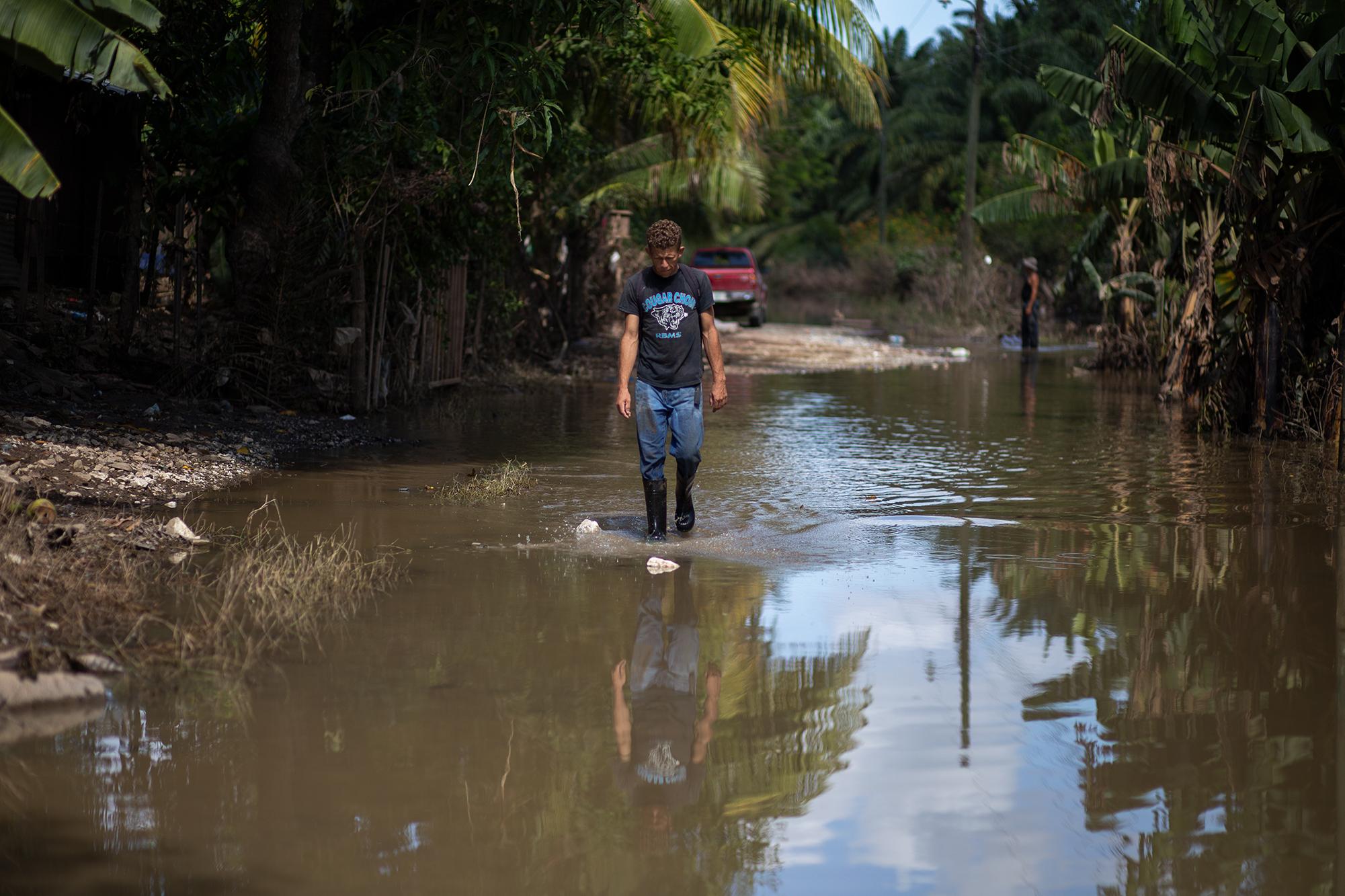 En la comunidad de Los Cruces en Baracoa, los estragos de la inundación siguen visibles. Un hombre atraviesa una calle convertida en río por las inundaciones tras el paso de la tormenta tropical Eta, en este punto se corta el paso hacia las comunidades adentro donde la crecida del río Chamelecón es superior. Baracoa, Cortés, 15 de noviembre de 2020. Foto: Martín Cálix.
