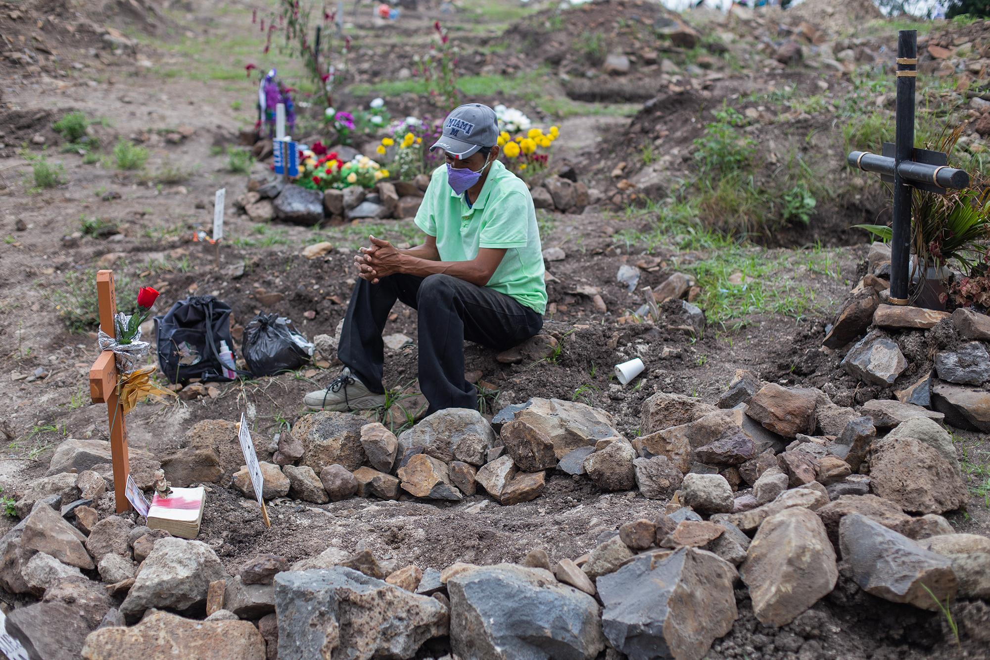 Sentado a un lado de la tumba que ha estado limpiando y adornando con piedras y recuerdos, José contempla la cruz que lleva inscrito el nombre de su madre. Comayagüela, 2 de noviembre de 2020. Foto: Martín Cálix.