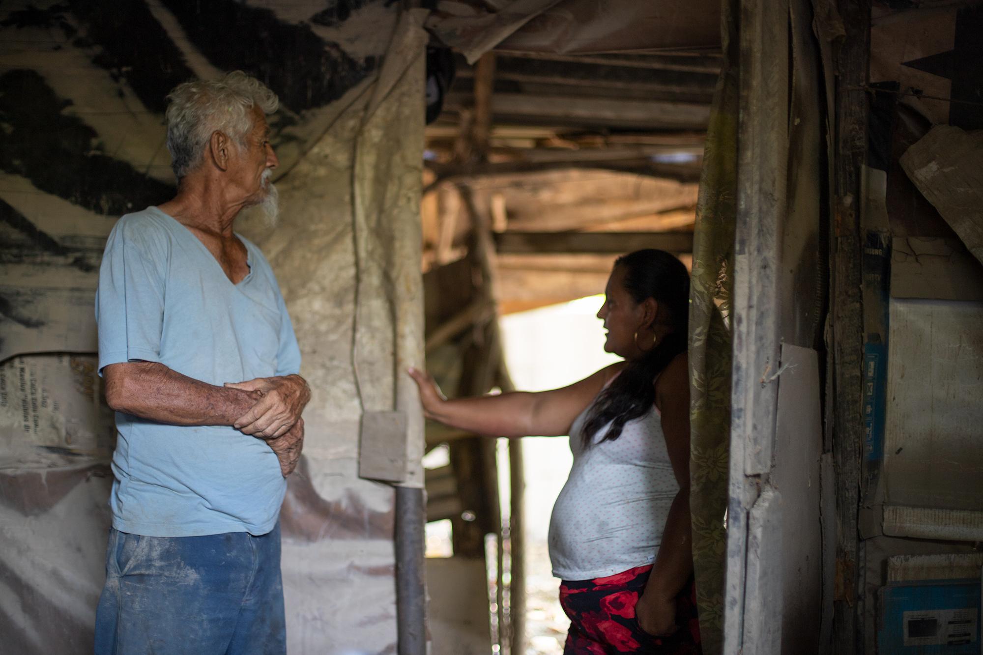 Rey de 72 años conversa con Jenny —esposa de un hijo suyo asesinado hace un año—, vive junto a su pareja de 71 años, esta pareja de ancianos lo perdieron todo. Rey cuenta que  la noche del pasado 4 de noviembre se acostaron creyendo que el agua no iba a llegar hasta su casa, pero en la madrugada del 5 de noviembre el agua invadió su casa y la de sus vecinos en la colonia Canaán del municipio de La Lima y lo perdieron todo. La Lima, Cortés, 13 de noviembre de 2020. Foto: Martín Cálix.