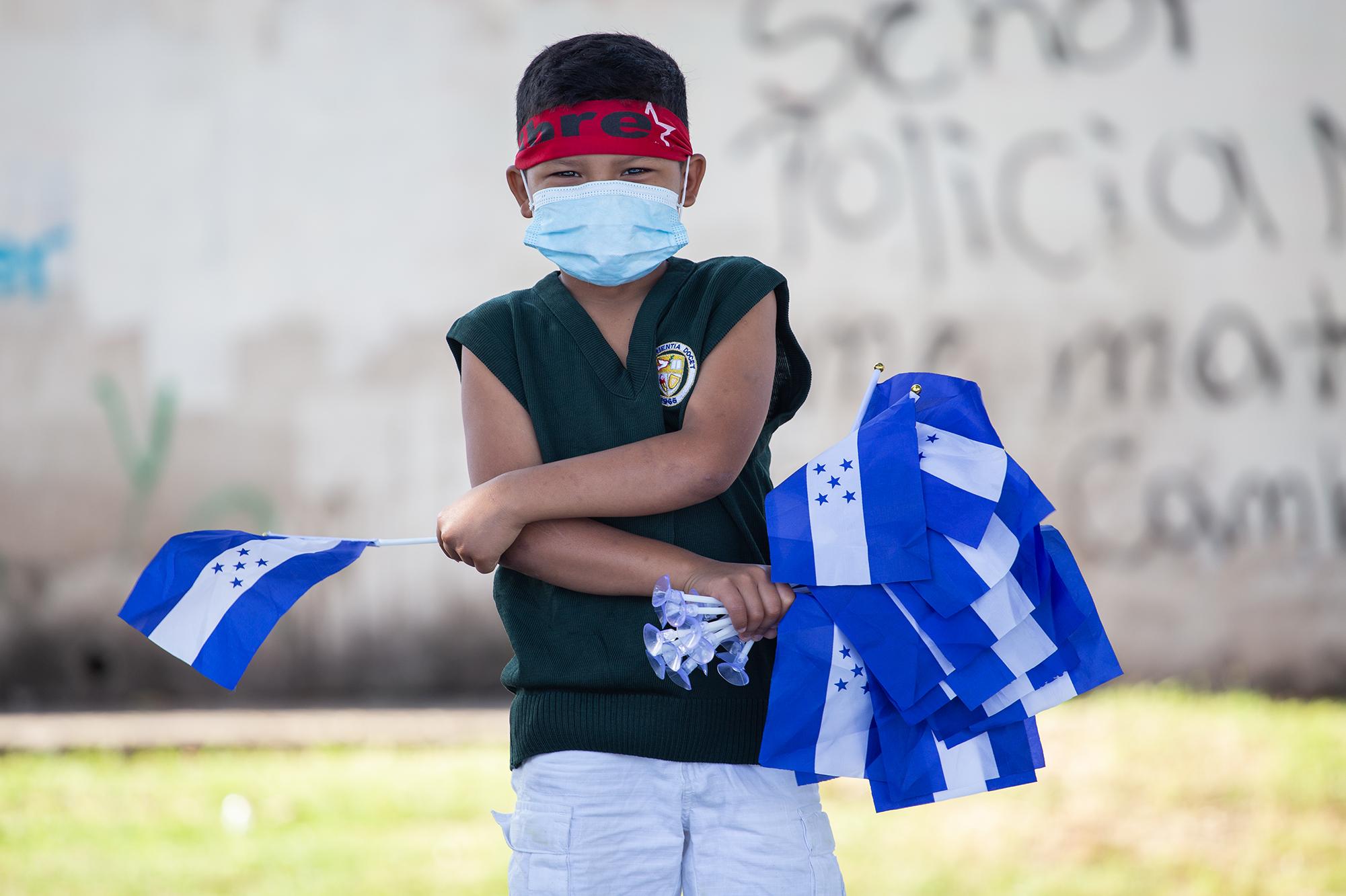 Un niño vende réplicas miniaturas de la bandera nacional durante una protesta. Tegucigalpa, 15 de septiembre de 2020. Foto: Martín Cálix.