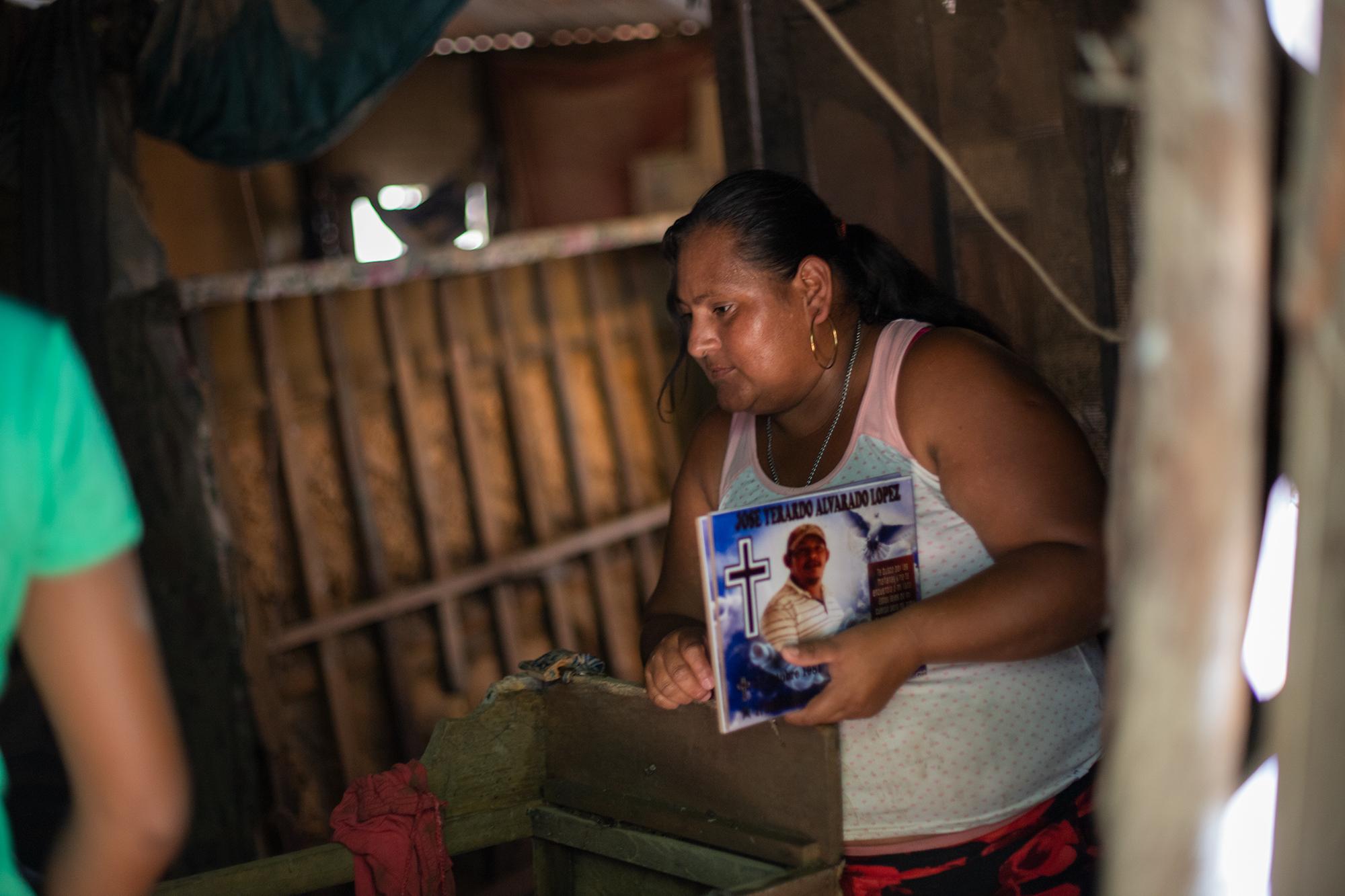Jenny de 34, es madre soltera de tres hijas, ellas perdieron todas sus pertenencias producto de las lluvias de la tormenta tropical Eta en la colonia Canaán, donde viven se llenara de agua. Jenny ha vuelto solo para recuperar las fotos de su hijo y de su esposo —quienes eran carreteros—, asesinados hace un año. La Lima, Cortés, 13 de noviembre de 2020. Foto: Martín Cálix.