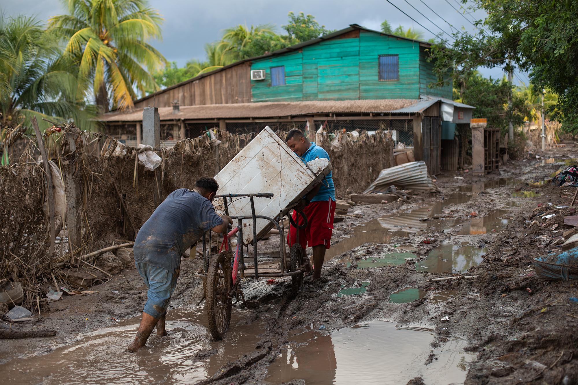Elman de 30 años y su amigo José Ángel de 24 han recuperado una lavadora luego de que bajara el agua de la inundación, tras el paso de la tormenta tropical Eta. San Manuel, Cortés, 16 de noviembre de 2020. Foto: Martín Cálix.