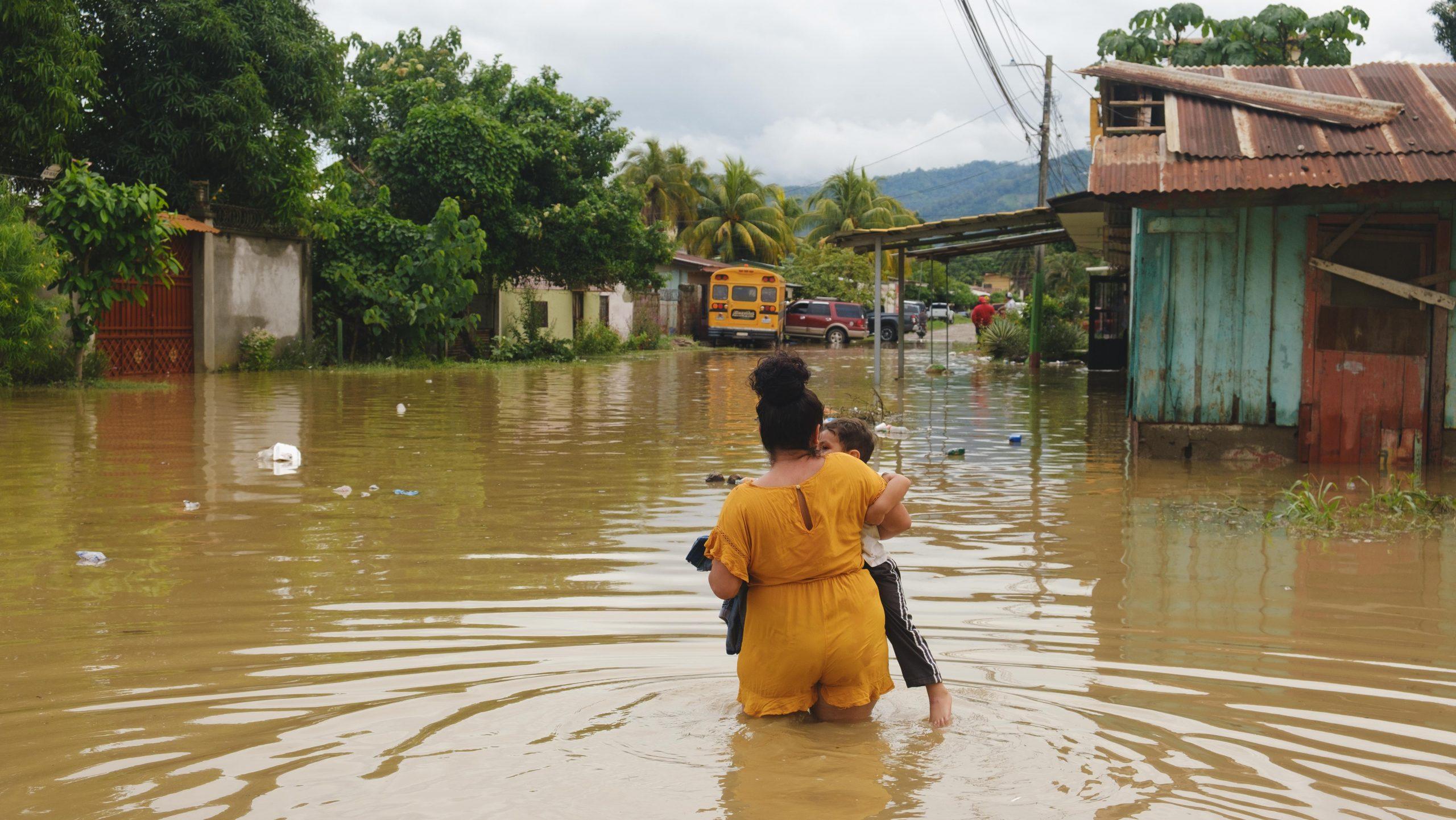 Una joven carga a su hijo a través de una calle inundada en el barrio San Miguel de El Progreso. 5 de noviembre de 2020. Foto: Deiby Yanes.