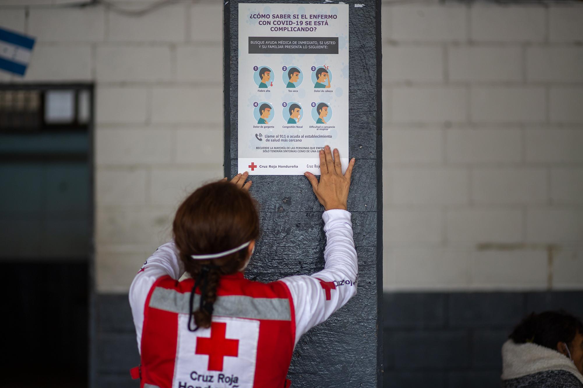 Una socorrista de la Cruz Roja Hondureña coloca un afiche que indica los síntomas para Covid-19 en el albergue del Instituto Central Vicente Cáceres. En el Distrito Central se les ha realizado la prueba para Covid-19 a las familias que se han refugiado en los albergues disponibles. Honduras ya registra 98,688 casos confirmados de Covid-19. Comayagüela, 5 de noviembre de 2020. Foto: Martín Cálix.
