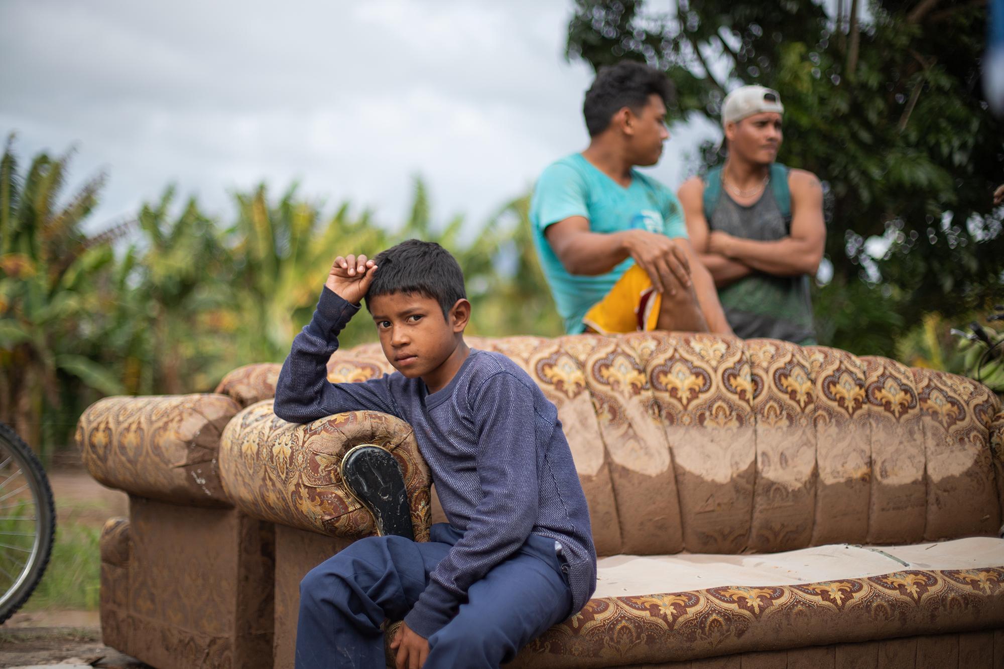 Sentado sobre un sofá rescatado de las inundaciones en la colonia La Democracia en la rivera del río Ulúa, Moises de 10 años, observa cómo el cause del río ha inundado los dos carriles de la CA-13 que conecta El Progreso con la ciudad de San Pedro Sula. Moises y su familia se han refugiado en un albergue improvisado con plásticos, trozos de madera, y láminas de zinc. San Manuel, Cortés, 18 de noviembre de 2020. Foto: Martín Cálix.
