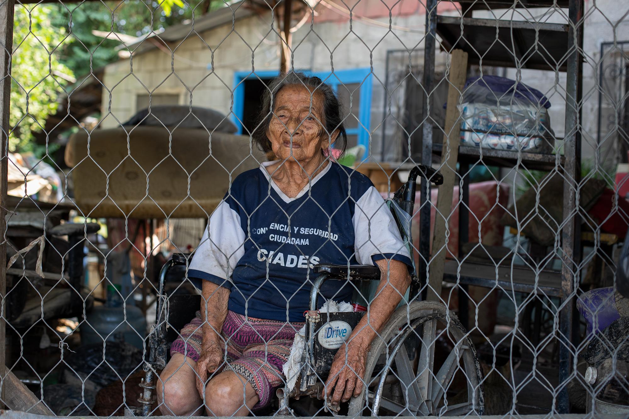 Seferina Lara, de 96 años, vive sola hace 20 años y ha quedado en silla de ruedas, ella vive en la colonia Los Ángeles, del municipio de La Lima, donde ha sido retratada. Esta anciana está a merced de la voluntad de las personas que quieran ayudarle con comida, o en caso de tener suerte, evacuándola de una casa que podría volverse a inundar. Su vida, la de sus gallinas y su gato correrían peligro. La Lima, Cortés, 13 de noviembre de 2020. Foto: Martín Cálix.
