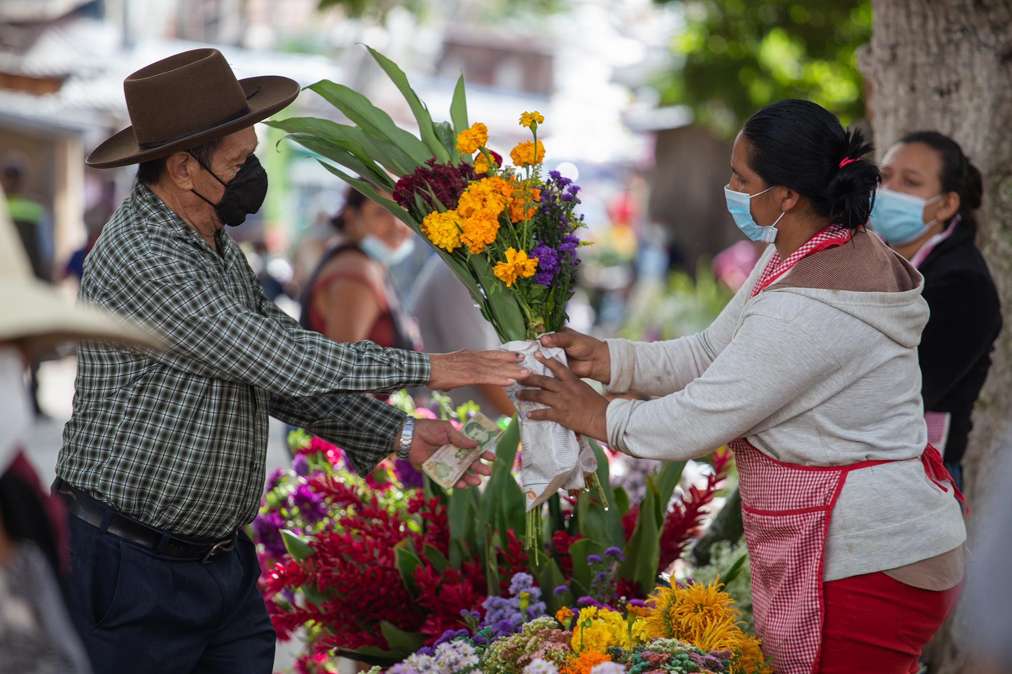 Un hombre compra flores en las afueras del Cementerio General de Comayagüela. 2 de noviembre de 2020. Foto: Martín Cálix.