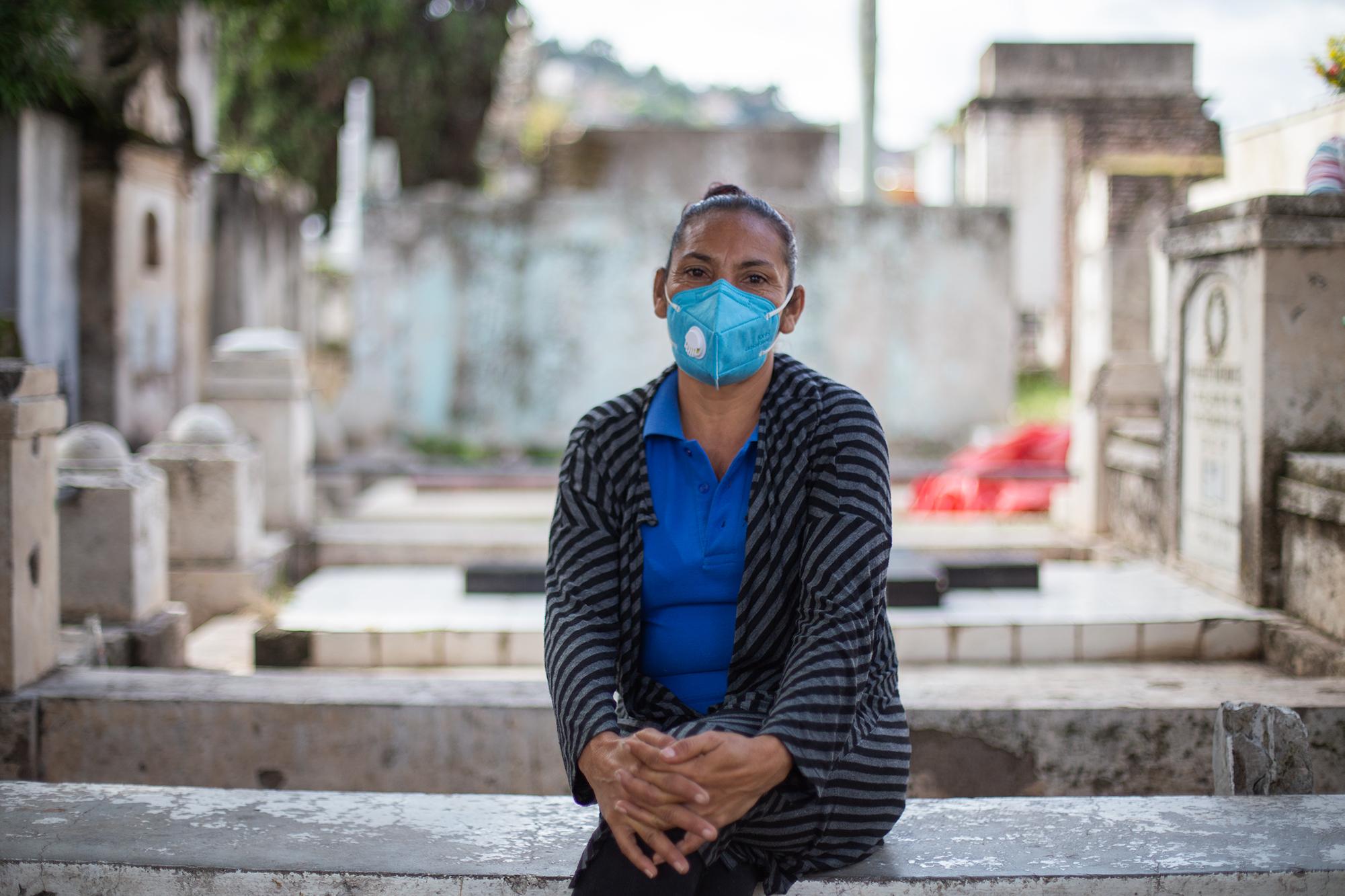 Suyapa Guillén, es retratada sobre una tumba en el Cementerio General de Comayagüela, esta microempresaria de chapeo trabaja como subcontratista para la Alcaldía Municipal del Distrito Central. Comayagüela, 2 de noviembre de 2020. Foto: Martín Cálix.