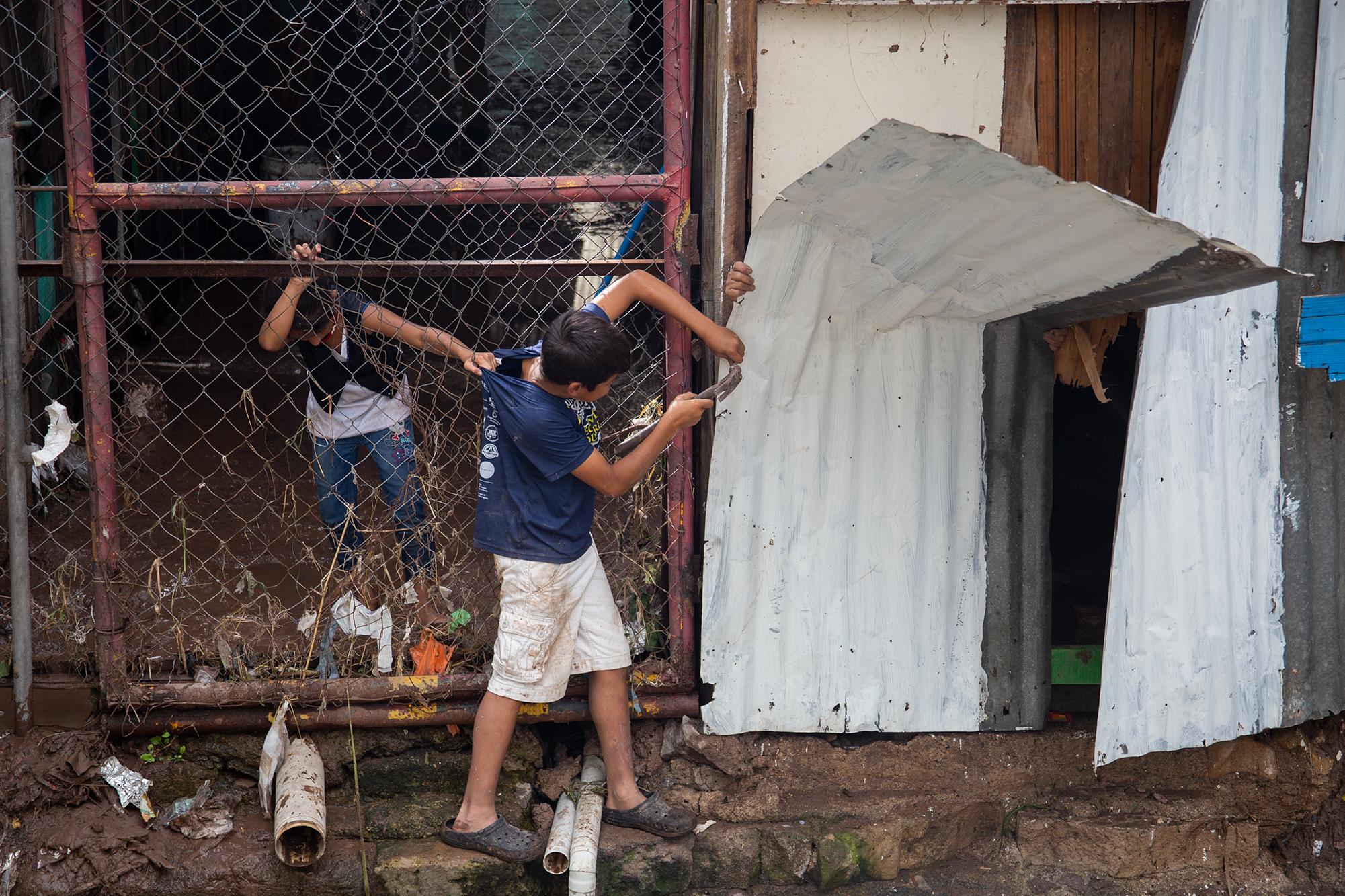Un niño es ayudado por un adulto y una niña mientras coloca una lamina en el local de su familia en el Mercado Emmanuel con la intención de proteger mejor su negocio ante la posibilidad de una nueva crecida del Río Choluteca. Comayagüela, 5 de noviembre de 2020. Foto: Martín Cálix.