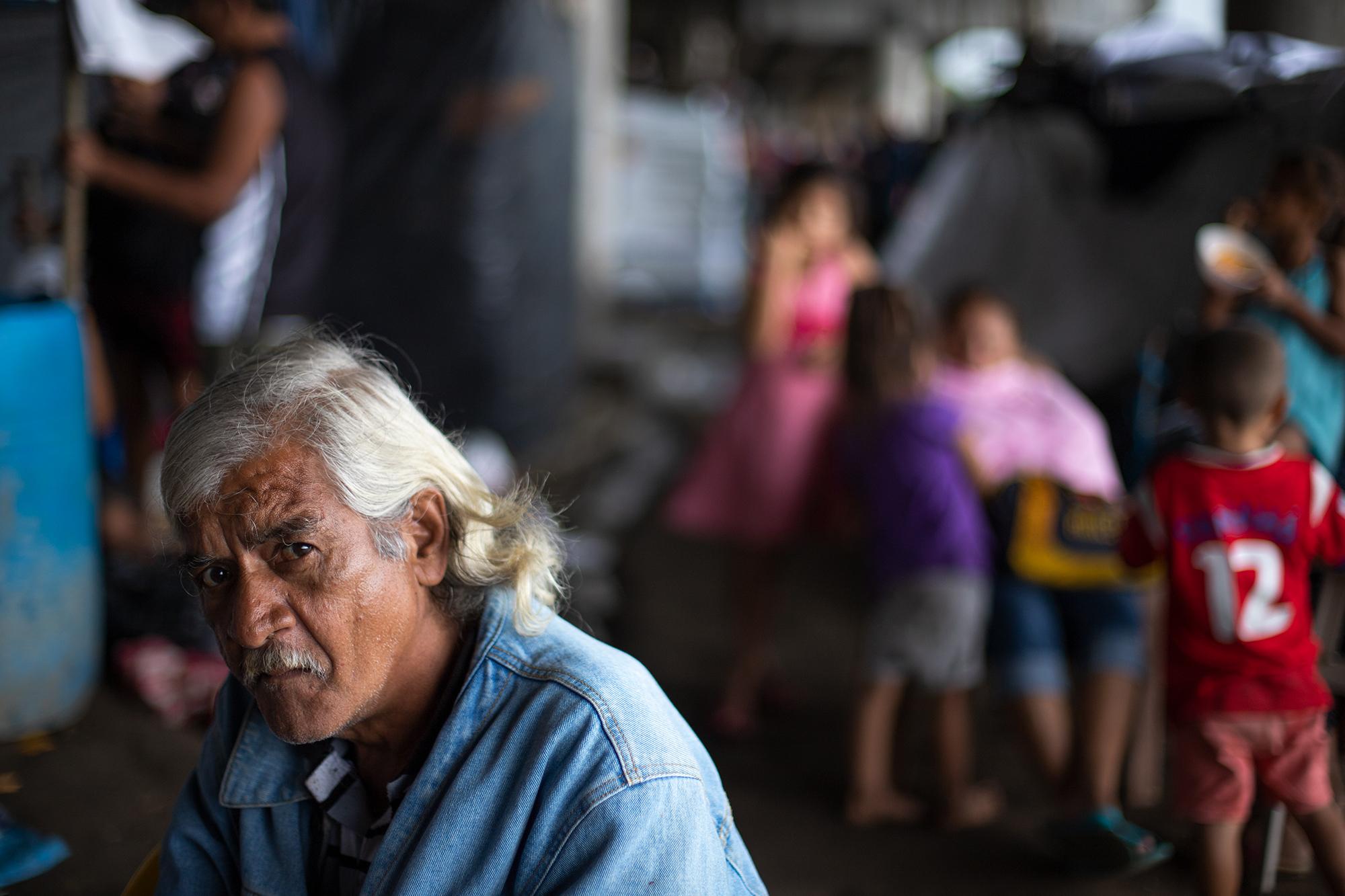 Santos España, de 64 años, ha quedado damnificado debajo del puente que conduce desde la ciudad de San Pedro Sula hacia el occidente hondureño. Santos explica que en varias ocasiones los militares les han querido trasladar a los albergues disponibles, pero las familias bajo este puente no confían en ninguna institución del Estado que quiere trasladarlos a albergues, ubicados en territorio controlado por la pandilla contraria a la de sus colonias, y donde esta violencia les pondría en mayor peligro. San Pedro Sula, 21 de noviembre de 2020. Foto: Martín Cálix.