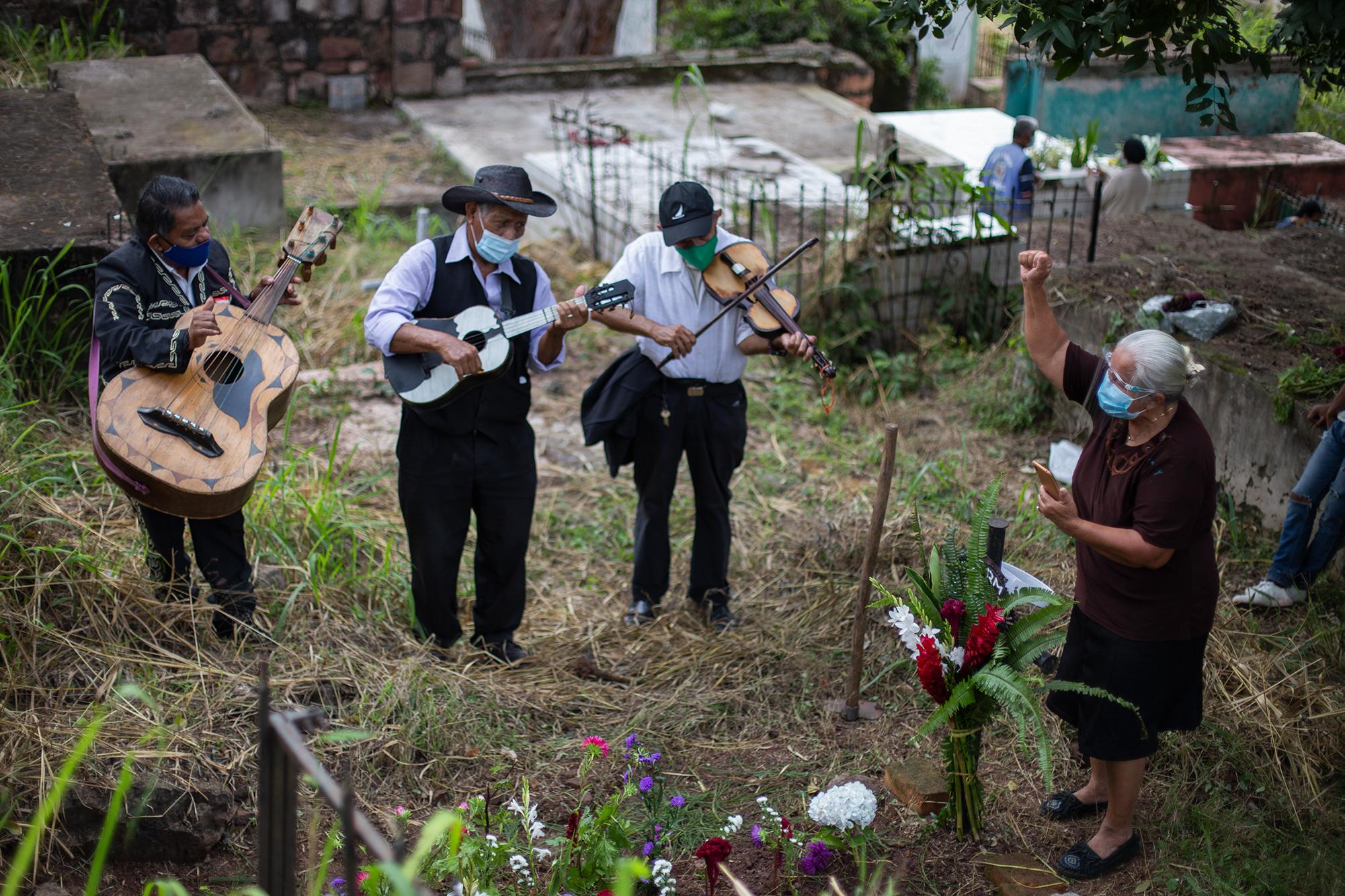 El mariachi Los Amigos Populares cantan la canción «Amor eterno» a solicitud de Josefina, quien ha llegado a coronar y limpiar la tumba de sus hijos. Comayagüela, 2 de noviembre de 2020. Foto: Martín Cálix.