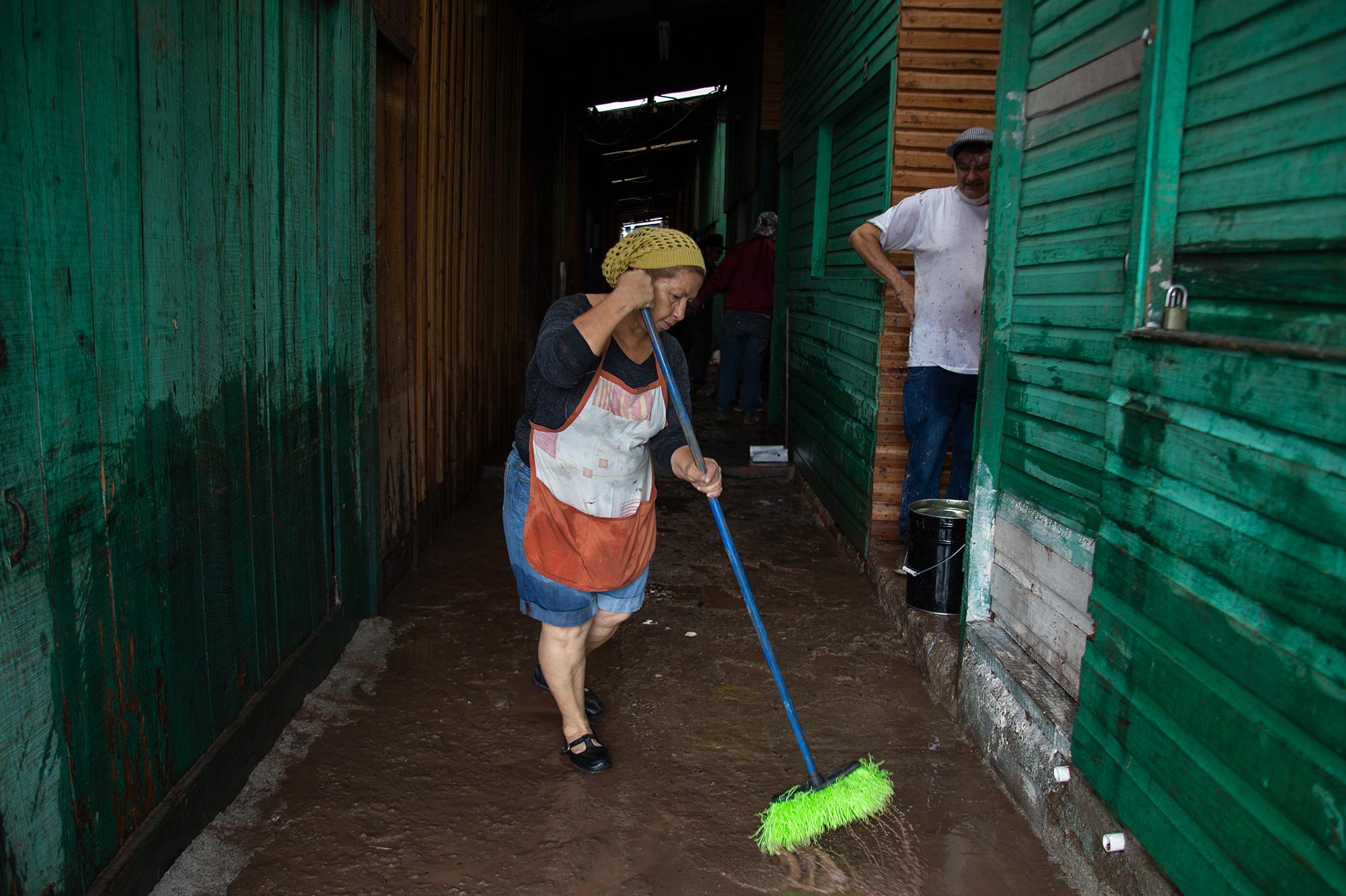 Una mujer barre para sacar el agua en el interior del Mercado Emmanuel que fue inundado por el Río Choluteca tras las constantes lluvias que dejó a su paso la tormenta tropical Eta. Comayagüela, 5 de noviembre de 2020. Foto: Martín Cálix.