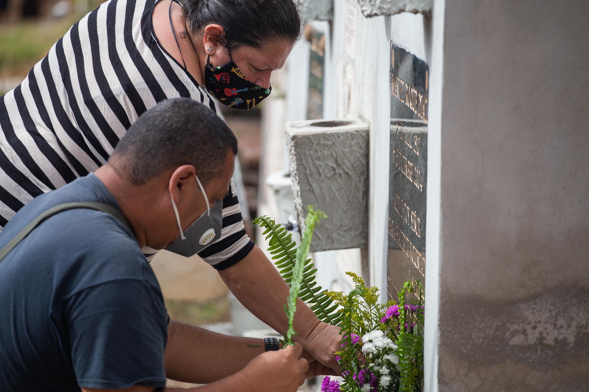 Wendy y Jorge limpian y adornan con flores los nichos de sus familiares en el Cementerio General del Distrito Central. Comayagüela, 2 de noviembre de 2020. Foto: Martín Cálix.