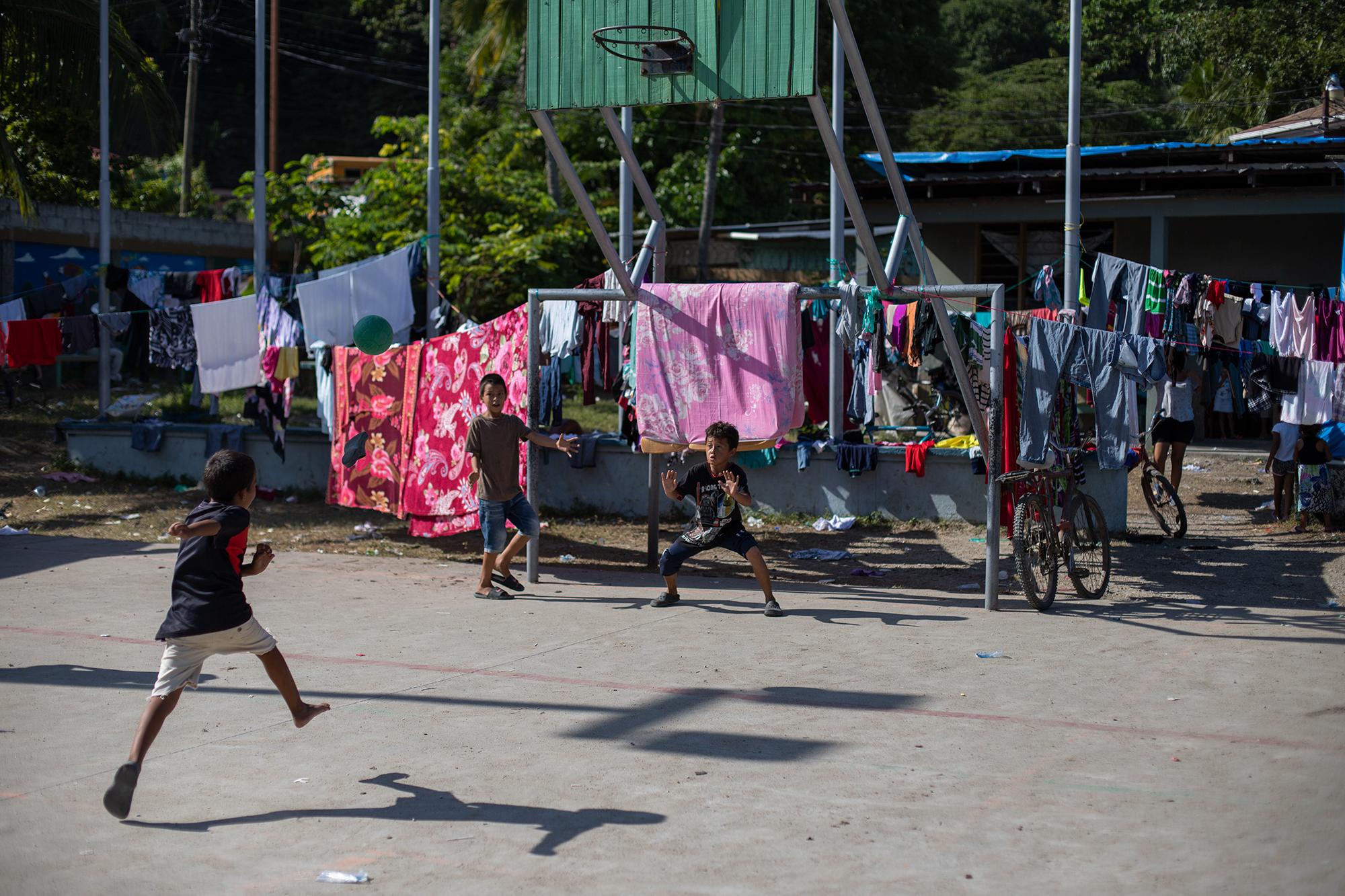 Tres niños juegan fútbol en la cancha de la Escuela Francisco Morazán de Baracoa, que ahora ha sido convertida en albergue para las personas afectadas por las inundaciones provocadas por las lluvias de la tormenta tropical Eta. Baracoa, Cortés, 15 de noviembre de 2020. Foto: Martín Cálix.