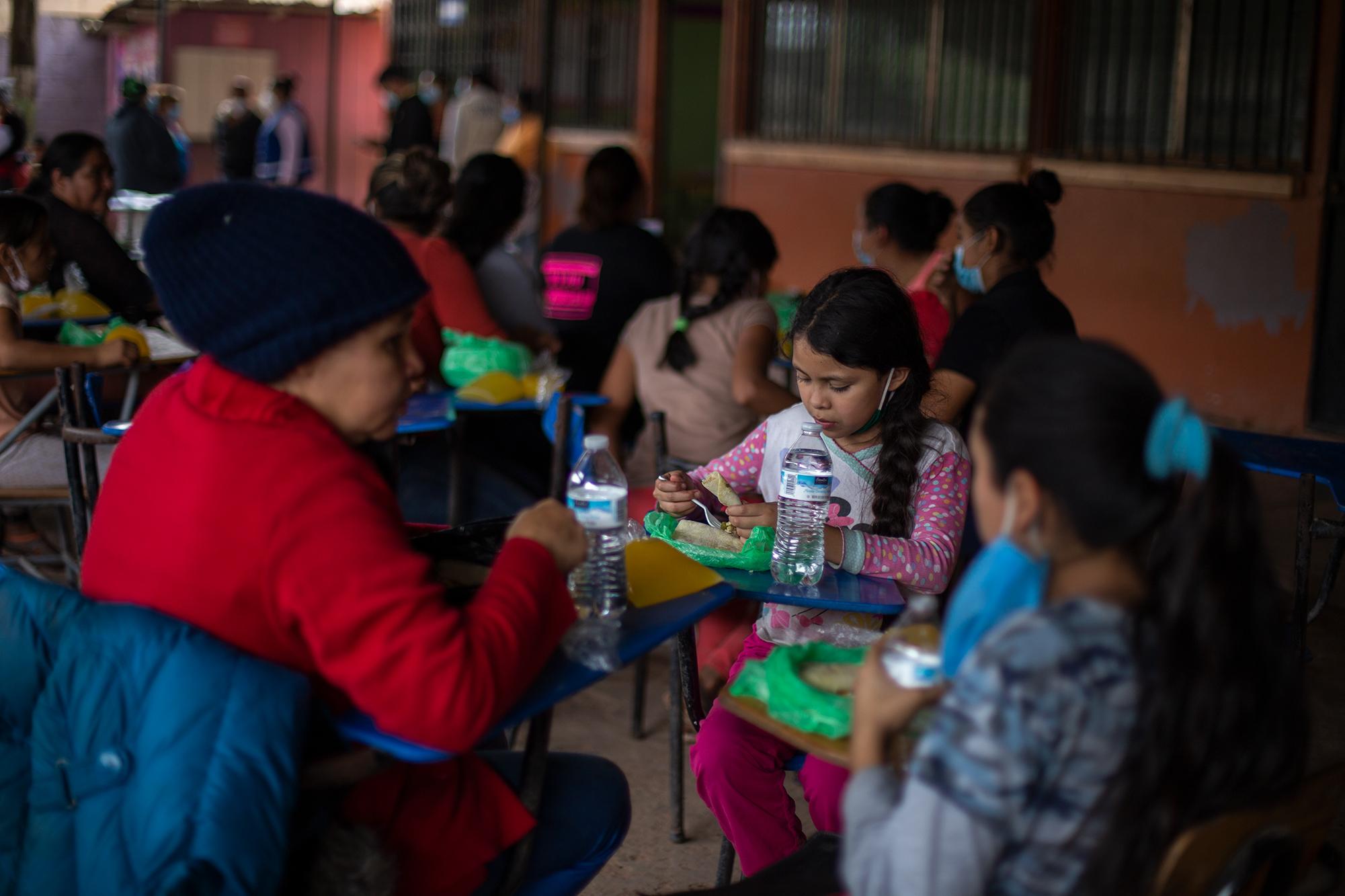 Una niña come junto a su familia en el albergue de la Escuela 17 de septiembre de la colonia Nueva Suyapa. Tegucigalpa, 5 de noviembre de 2020. Foto: Martín Cálix.