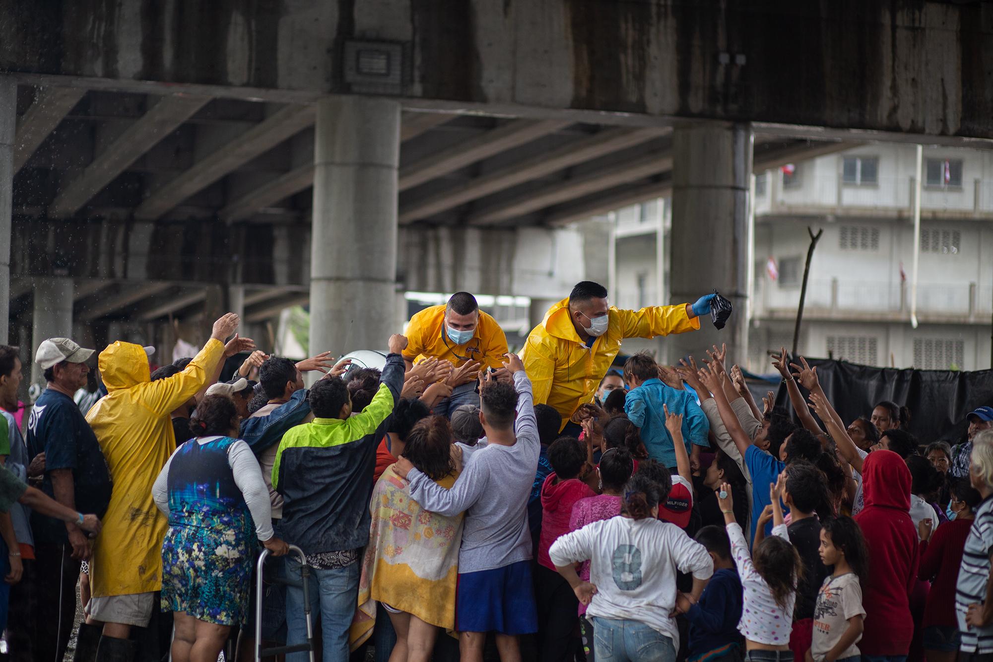 Trabajadores de una empresa procesadora de pollo regalan tamales y jugos a las familias damnificadas del sector Chamelecón, en los bajos del puente de la salida a occidente. San Pedro Sula, 21 de noviembre de 2020. Foto: Martín Cálix.