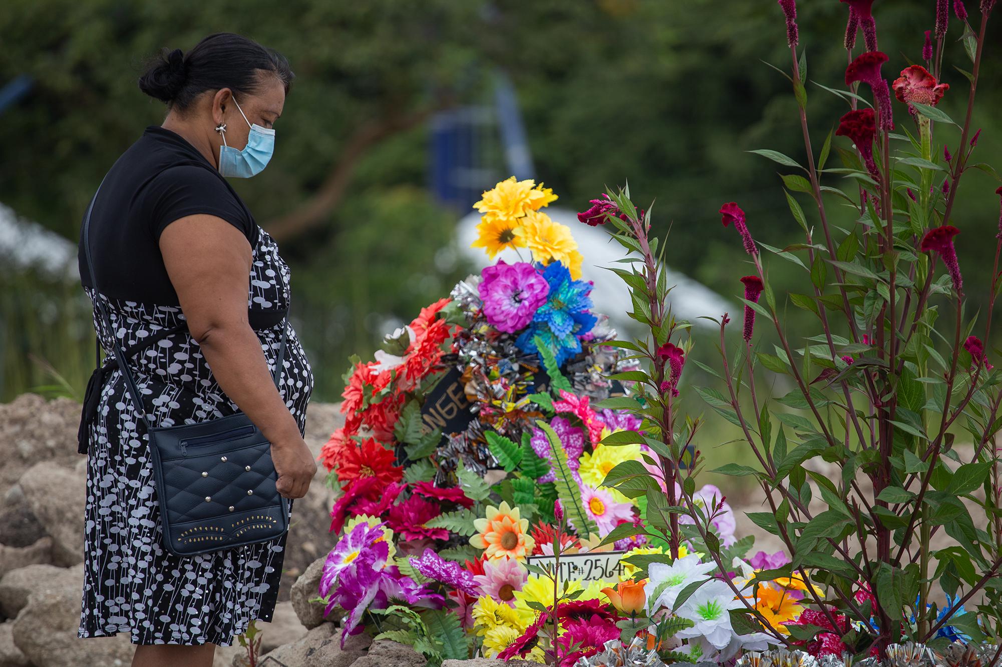Gladis de 45 años ha limpiado y adornado con flores la tumba de su madre que falleció a los 69 años en el Hospital Escuela Universitario a causa de la Covid-19. Comayagüela, 2 de noviembre de 2020. Foto: Martín Cálix.
