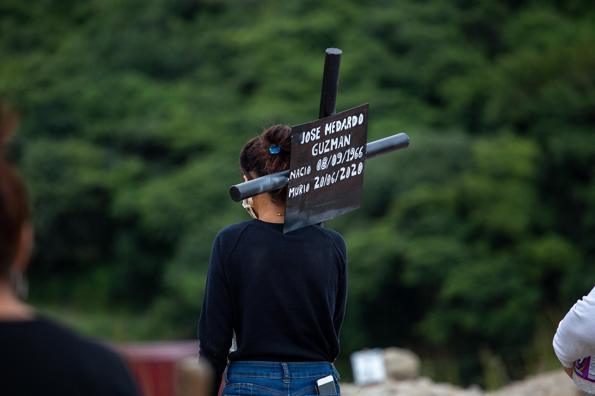 Una joven carga una cruz de metal de su familiar fallecido por Covid-19 el pasado 20 de junio. Comayagüela, 2 de noviembre de 2020. Foto: Martín Cálix.