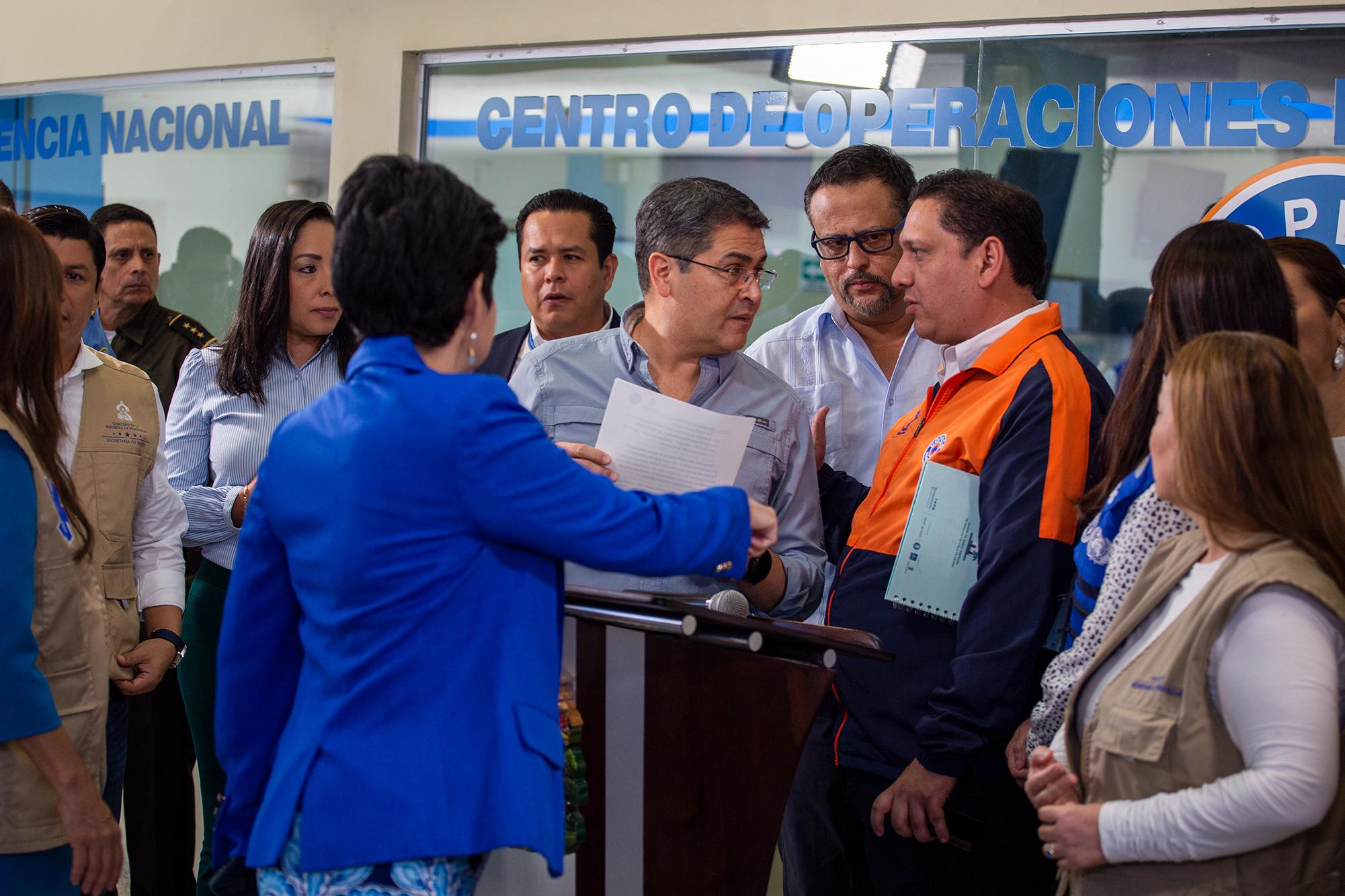 Juan Orlando Hernández, presidente de la República y Gabriel Rubí, exministro comisionado de Copeco, al finalizar una conferencia de prensa donde se explicó que las instituciones estaban trabajando para responder a la crisis del COVID 19. Cuando se hizo esta fotografía el país registraba apenas dos casos positivos, en la actualidad, Honduras cierra el año con una cifra que supera los 114,000 infectados y casi 3000 muertes por COVID-19 a nivel nacional, según cifras oficiales del Gobierno hondureño. Tegucigalpa, 11 de marzo de 2020. Foto: Martín Cálix.