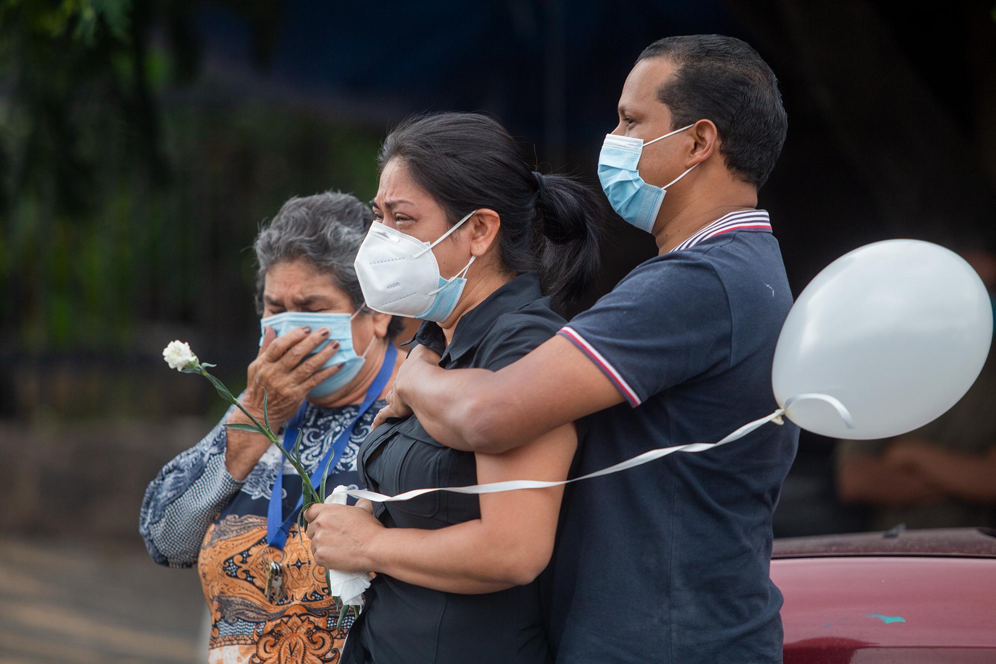 Honduras registra más de 3000 muertes por COVID-19, según cifras oficiales del Gobierno hondureño a través del Sistema Nacional de Gestión de Riesgo, el 28.9 % de estas se registran en el departamento de Cortés, esto convierte al departamento de Cortés en la zona más afectada por la pandemia en 2020. En la fotografía, familiares del periodista Pablo Matamoros lloran su fallecimiento a causa de la COVID-19 en un cementerio de la capital hondureña. Esta fotografía fue la portada del podcast Hemos perdido, que aborda el duelo y la muerte por COVID-19. Tegucigalpa, 2 de julio de 2020. Foto: Martín Cálix.