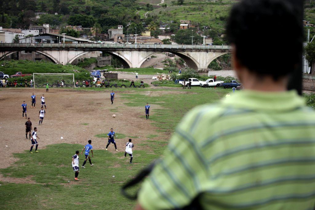 Un aficionado observa desde el puente soberanía un partido de fútbol