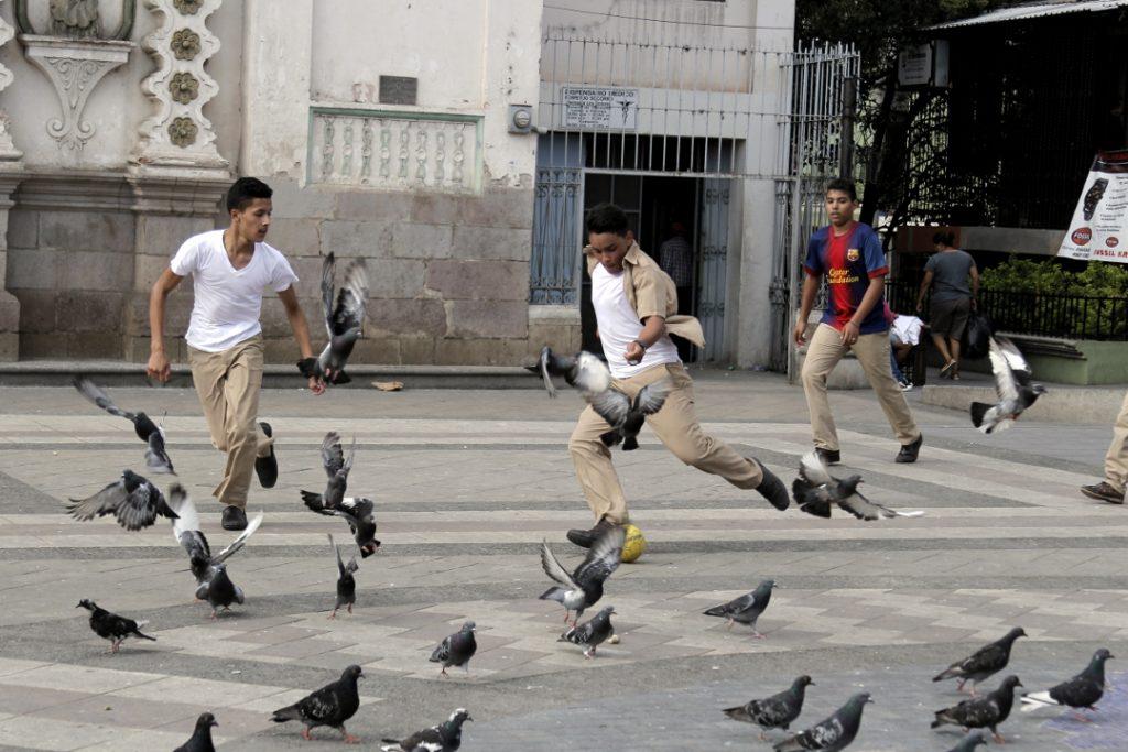 Chicos de un instituto de secundaria en Tegucigalpa juegan en la Plaza Los Dolores.