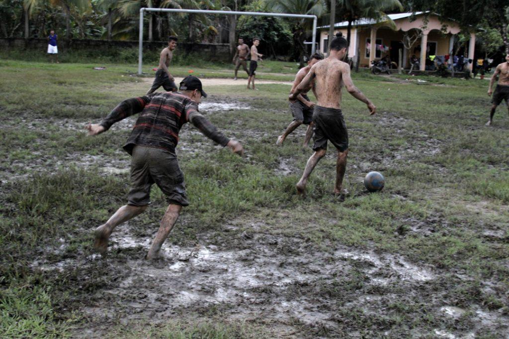 Jóvenes de la comunidad Guadalupe Carney en el Valle del Aguán juegan en la cancha de la comunidad