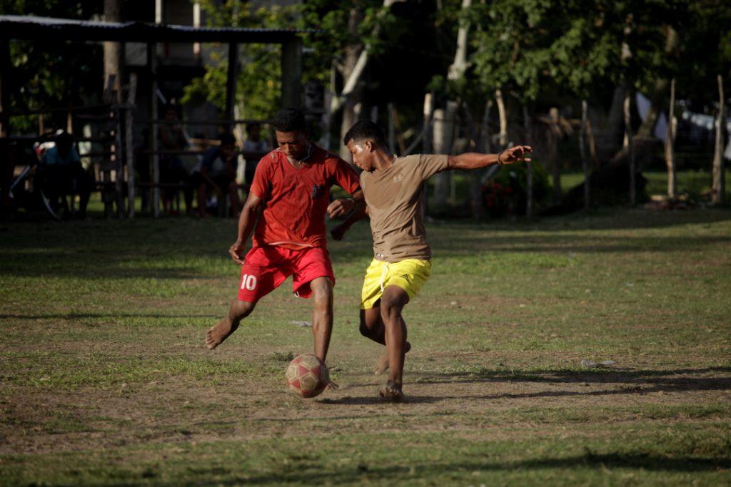 Jóvenes pescadores de la comunidad de Cauquira en la moskitia juegan fútbol en una cancha que es atravesada por la única calle del pueblo