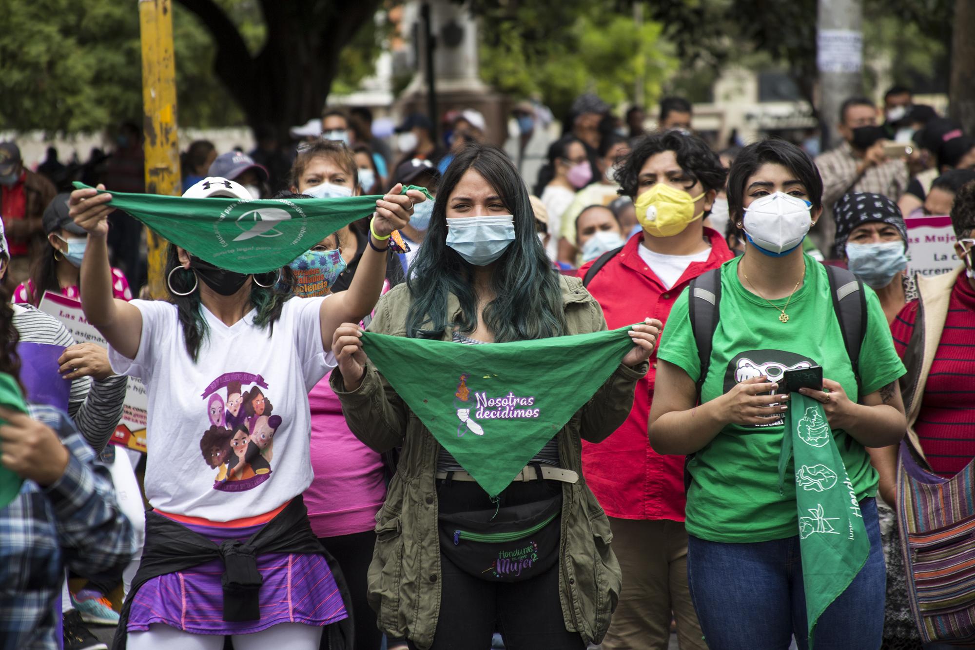 Feministas e integrantes de la diversidad sostienen pañuelos verdes en alto durante el plantón realizado frente al cordón policial que le impidió el paso a la movilización hasta el Congreso. Tegucigalpa,  25 de enero de 2021. Foto: Ezequiel Sánchez / Contracorriente.