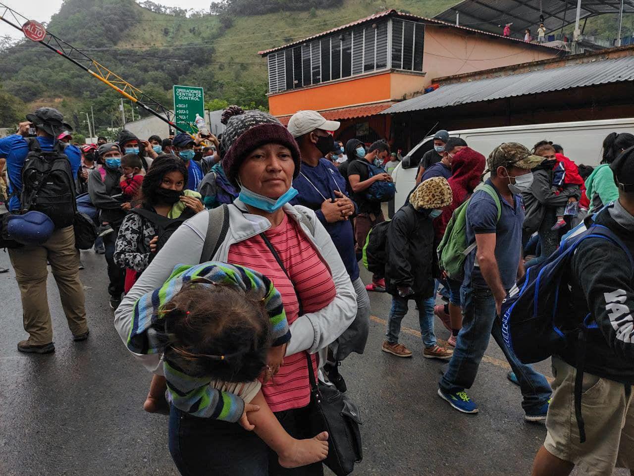 Una madre hondureña cruza la frontera entre Honduras y Guatemala cargando a su pequeña en brazos. Los migrantes rompieron un cerco formado por elementos de la Policía Militar. El Florido, frontera de Honduras y Guatemala, 16 de enero de 2021. Foto: Deiby Yánes.