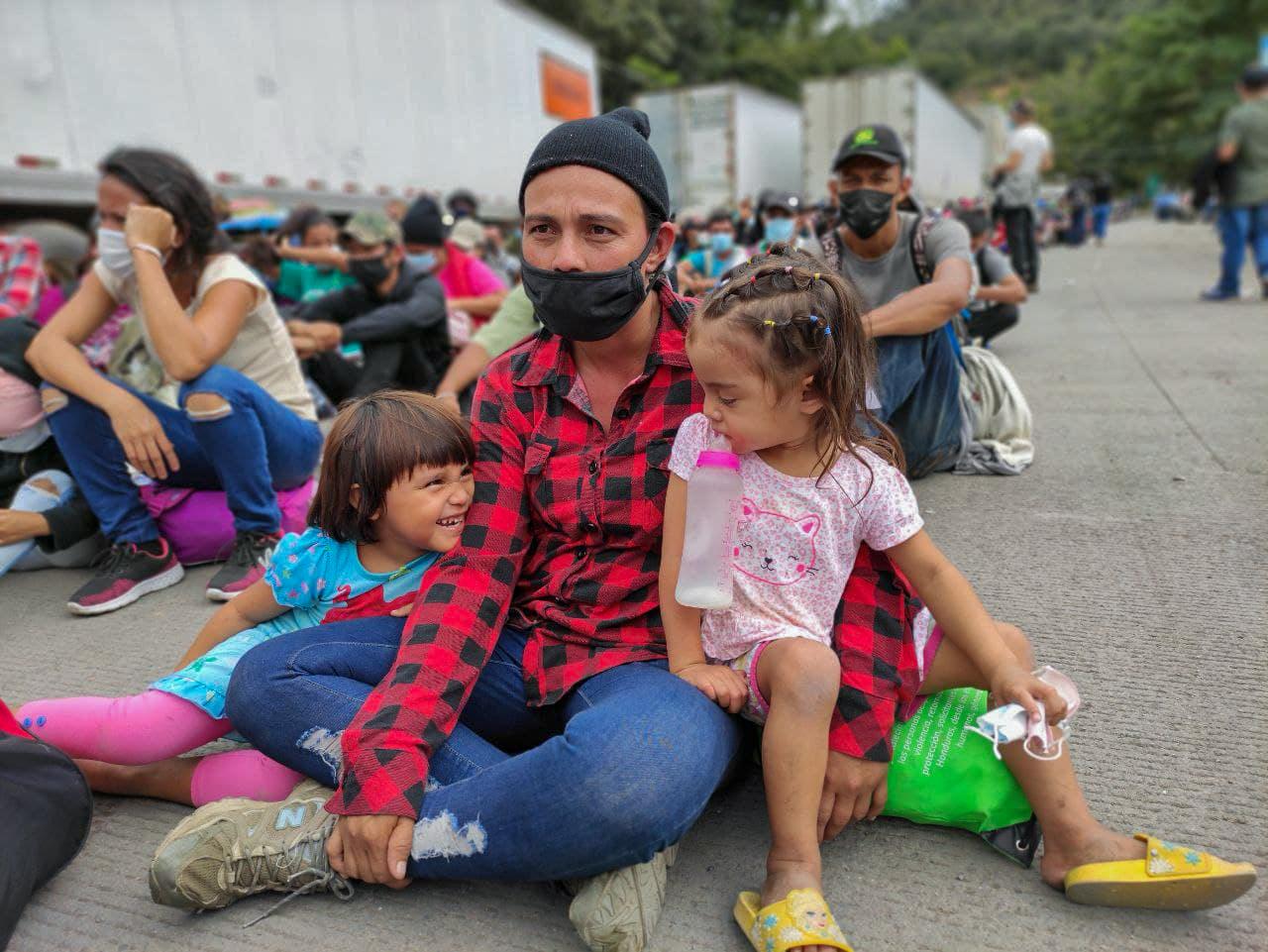Una madre con sus hijas esperan sentadas junto al resto de la caravana a que la policía guatemalteca les permita el paso. Los migrantes entonaron el himno nacional de Honduras mientras esperaban. El Florido, frontera de Honduras y Guatemala, 16 de enero de 2021. Foto: Deiby Yánes.