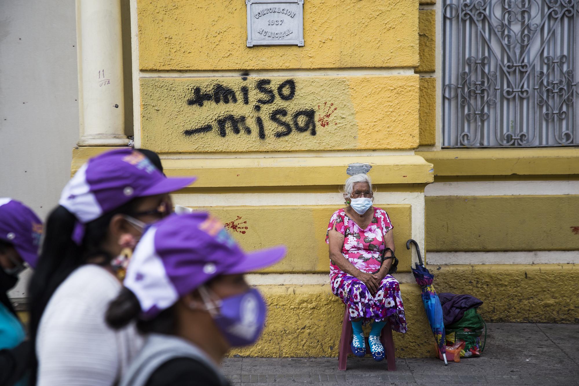 Vendedora ambulante de la tercera edad ve pasar la movilización feminista frente a su asiento mientras se acercan al Congreso Nacional. Tegucigalpa,  25 de enero de 2021. Foto: Ezequiel Sánchez / Contracorriente.