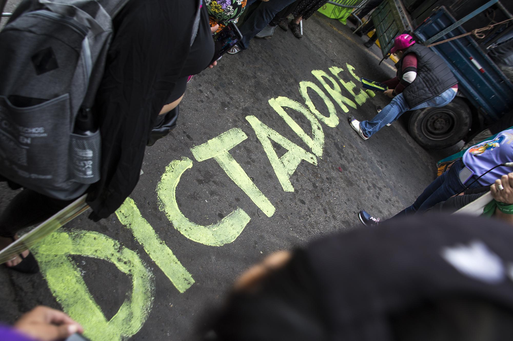 Una mujer realiza una pinta frente a la valla instalada por la policía para impedir el paso de la movilización hasta el Congreso Nacional. Tegucigalpa,  25 de enero de 2021. Foto: Ezequiel Sánchez / Contracorriente.