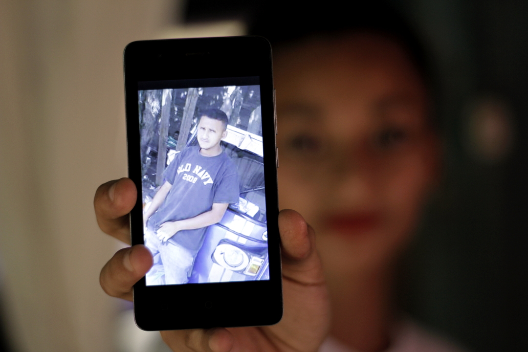 Indira (18 años), sostiene en su mano un teléfono celular mostrando la foto de su hermano Maynor Ariel Reyes Mejía (24 años), preso en El Pozo.