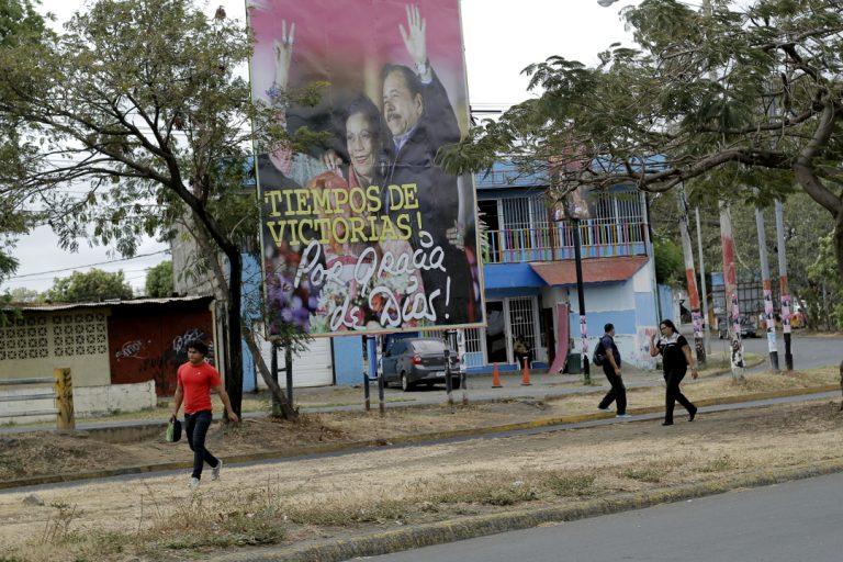Algunas personas pasan frente a una valla de propaganda oficial del gobierno sandinista