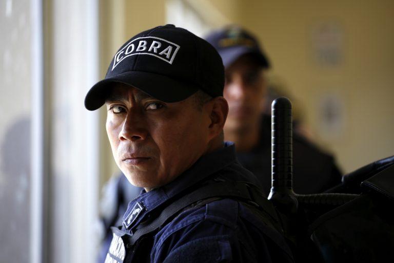 Un oficial de las Fuerzas Especiales Cobras ve en dirección a la prensa con expresión de cansancio