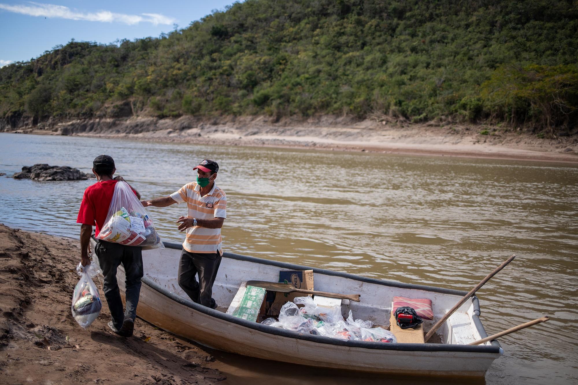 Visitación Paz Muñoz, de 65 años y camiseta a rayas, conduce la lancha del Patronato de la comunidad de La Isla Colina, para ayudar a que sus vecinos logren cruzar de un lado a otro el río Ulúa. Santa Bárbara, 25 de enero de 2021. Foto: Martín Cálix.